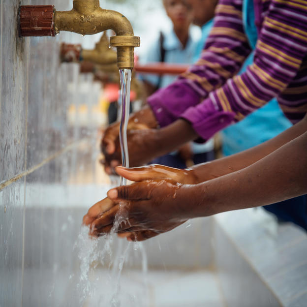 Students wash their hands at the newly installed taps and handwashing station at Mahubo 14 Primary School in Eduardo Mondlane, Boane District, Mozambique.