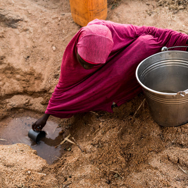 Naja'atu (15) scoops water that she has dug from the ground near a stream in Kissa community, Kwaja village, Adamawa. Nigeria. February 2021
