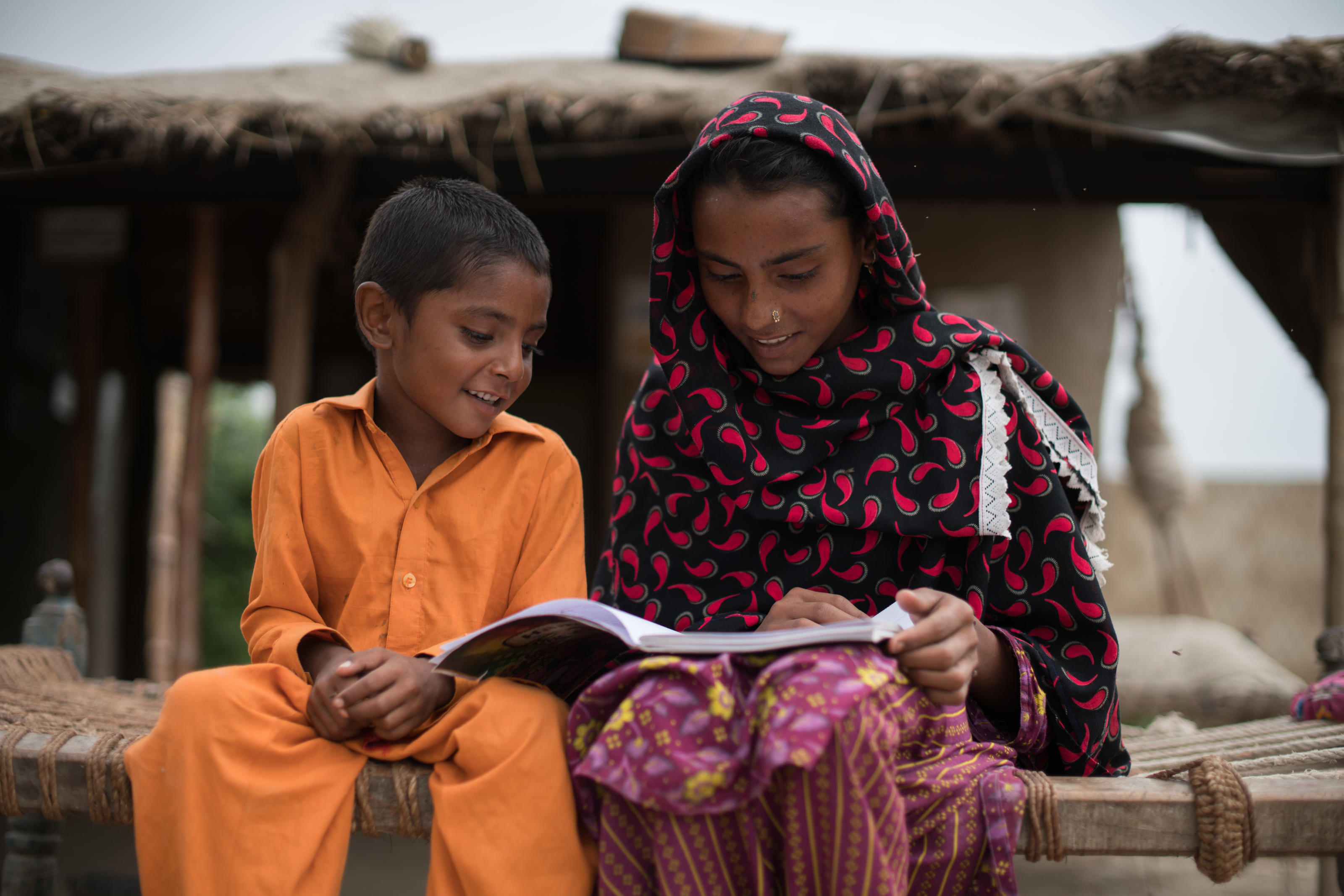 Sonia, 15, student of class 5, teaching her younger brother in her home in the village of Shevo Kolhi, Union Council Kadi Kazia, District Badin, Province Sindh, Pakistan, July 2017