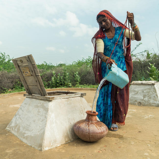 Diya, 35, fetching water from the rainwater harvesting tank in her house in the village of Leeria Bheel, Union Council Kantio, Taluka Chachro, District Tharparkar, Province Sindh, Pakistan, August 2017