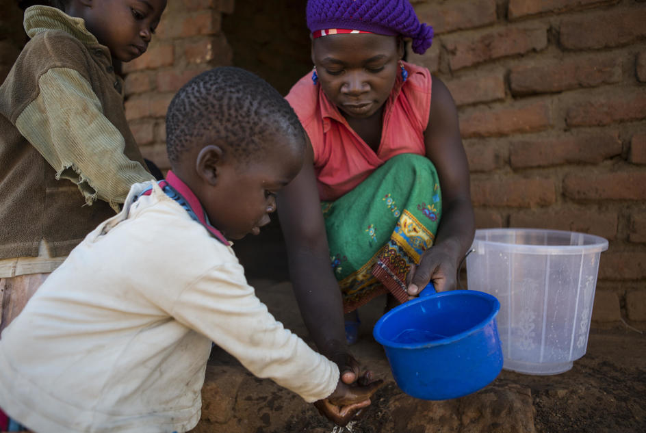 Zione Petulo helps the children wash their hands before eating breakfast outside their home in Malawi.