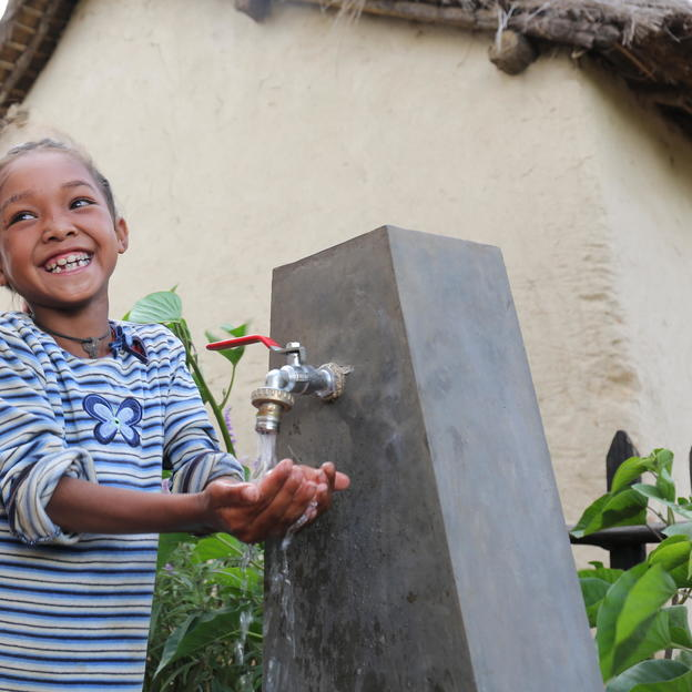 Salohy drinks water from the new tap in her village in Madagascar.