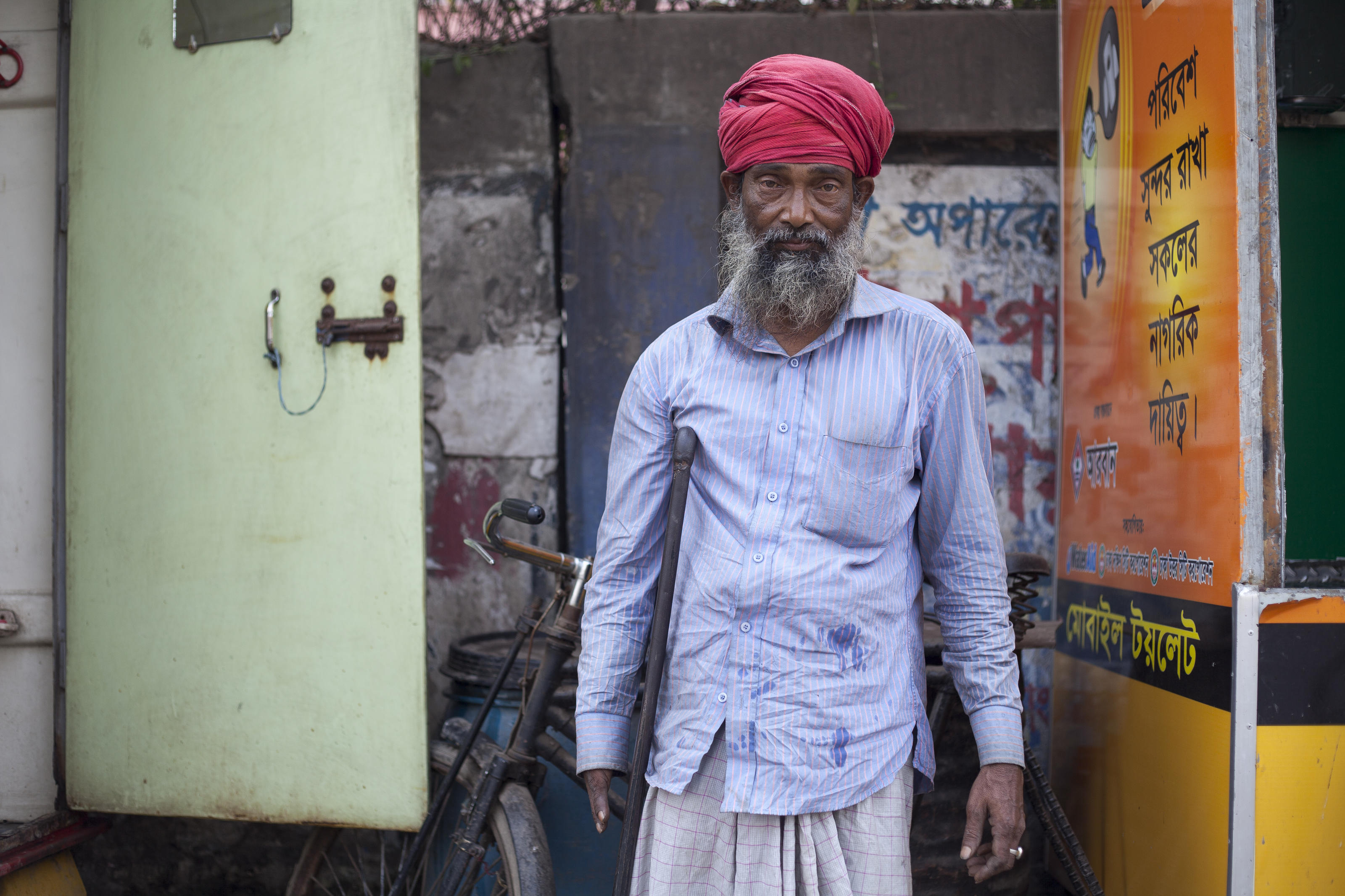 Amin, 52, mobile toilet keeper, on the street at a technical signal crossing, supported by WaterAid, in Dhaka, Bangladesh