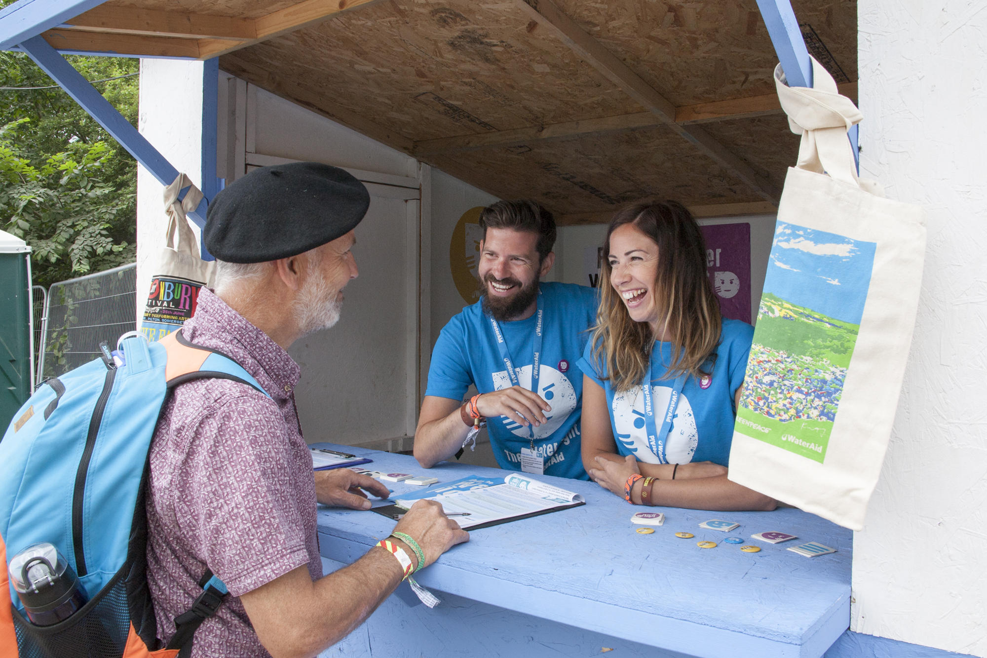 A WaterAid volunteer and staff member manage the Water Kiosk at Glastonbury festival, June 2017.