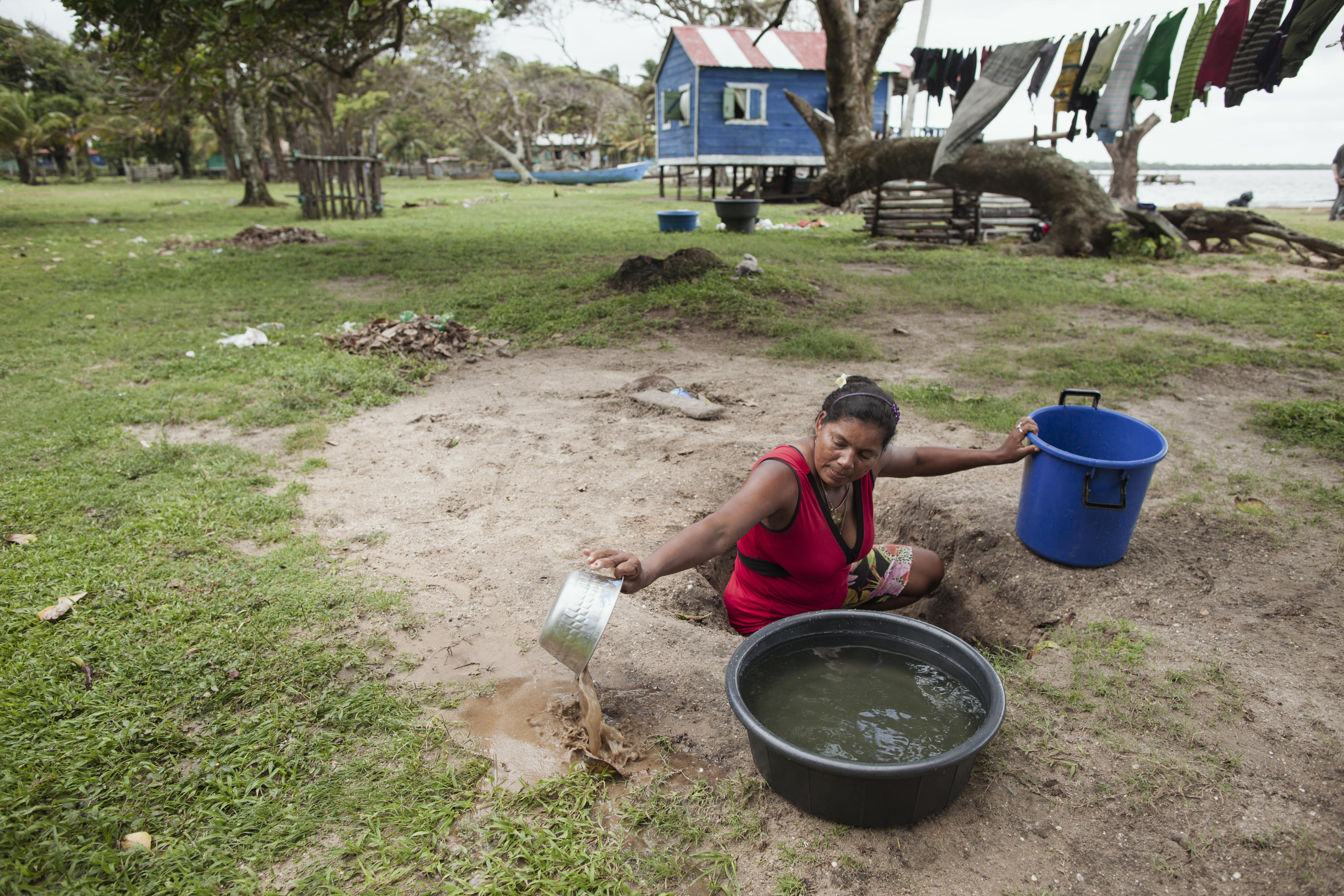 Carla Espinoza Urbina, 37 cleaning the water of the well by taking the sandy water out. As the well the family normally uses has been flooded after heavy rains, she had to move to another one 10 min away from her house. Wawa Bar, Bilwi, Nicaragua, 2015.