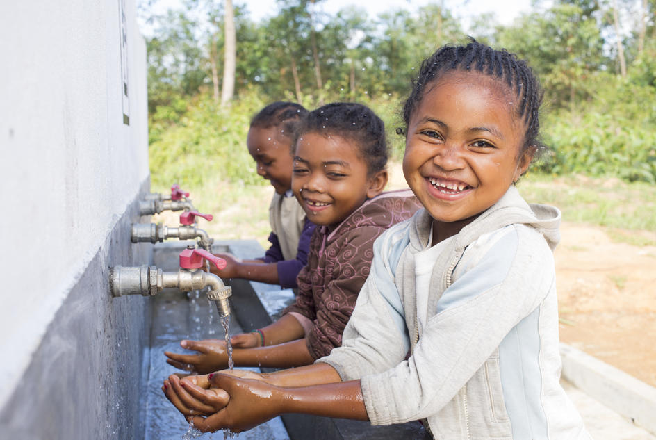 Cynthia Ramaholinirina, 6, with some of her classmates washing hands at the handwashing station of their Primary school of Mahavoky village, Belavabary commune, Moramanga district, Alaotra Mangoro region, Madagascar. May 2017.