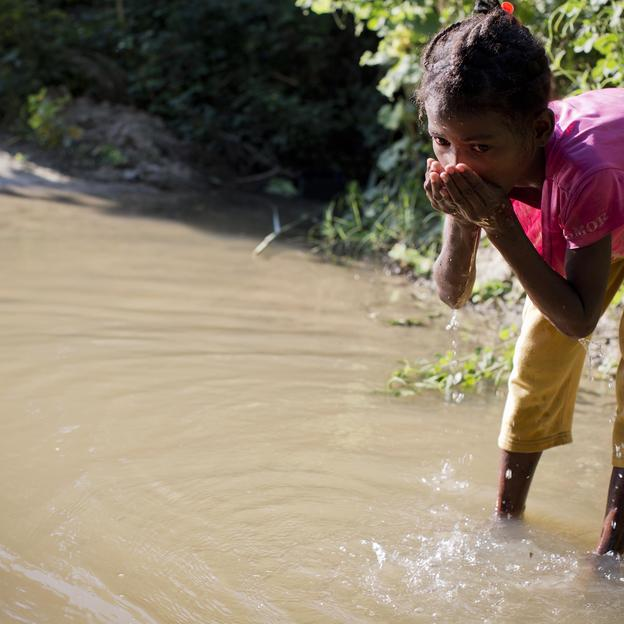 A young girl drinks water from a stream in Madagascar.