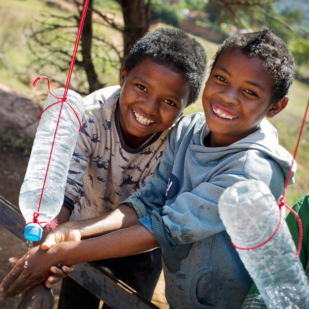 Children demonstrate how to use the tippy tap handwashing system at their school in Madagascar.