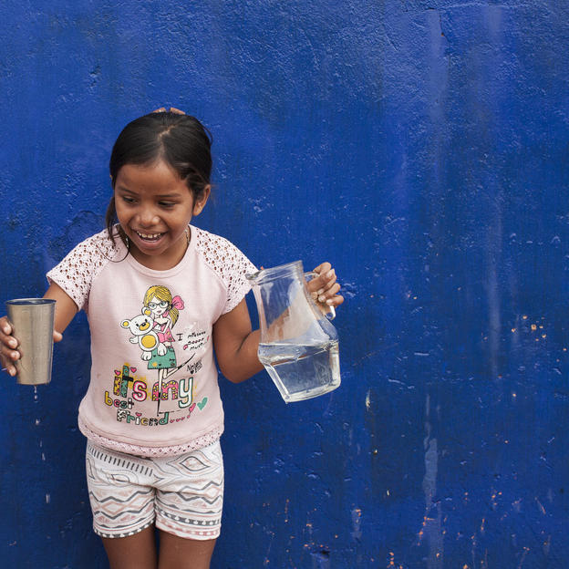 Wendi, 9, holds a jug and a glass of water near her house in Colombia.