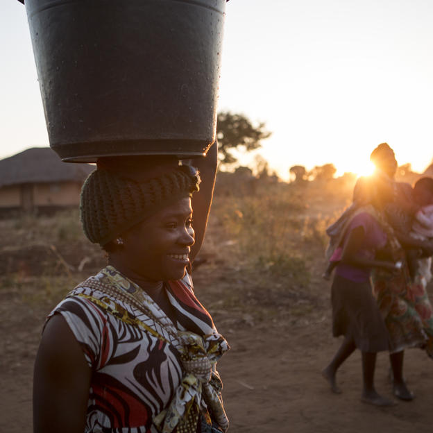 Howa carries a bucket of clean water which she has collected from the hand pump in a village in Salima District, Malawi, June 2016.