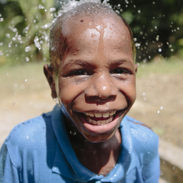 Alford, 5, washing at tapstand in Papua New Guinea