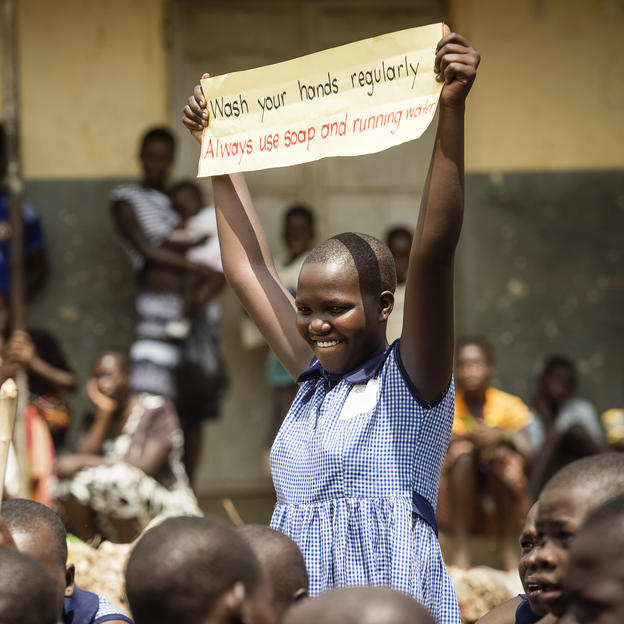 Sharon holds up a sign during a march to raise awareness of WASH practices in Uganda