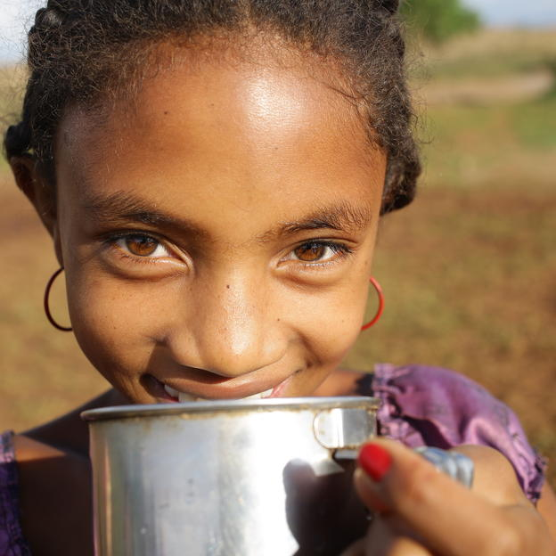 Aurelia, drinking clean water at the water point in her village, Bongolava region, Madagascar.