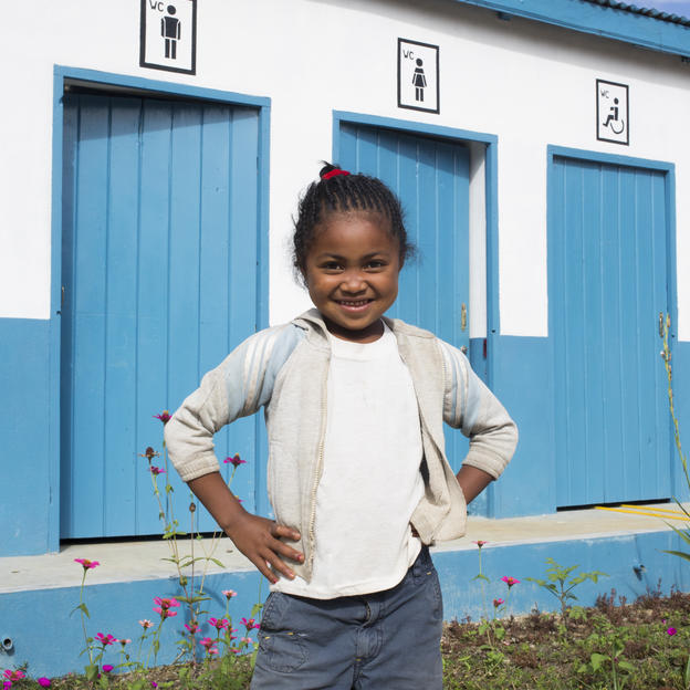 Cynthia posing in front of her school's new toilet block in Madagascar.