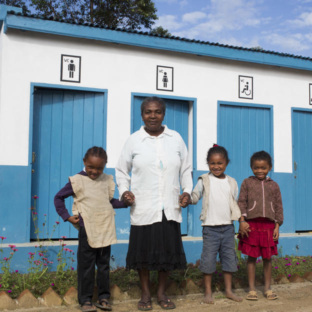 Marionette and three children stand outside their newly built toilet block in Madagascar.