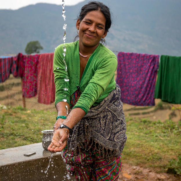 Mandari washing her hands in the tapstand, Nepal.