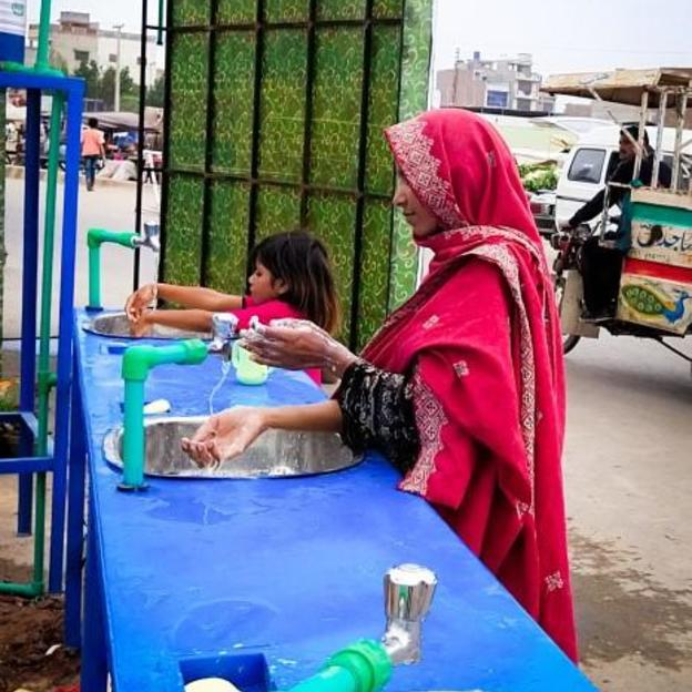 People washing their hands at two of the six handwashing stations WaterAid installed in Multan City to combat the spread of COVID-19. COVID-19 response Pakistan. April 2020