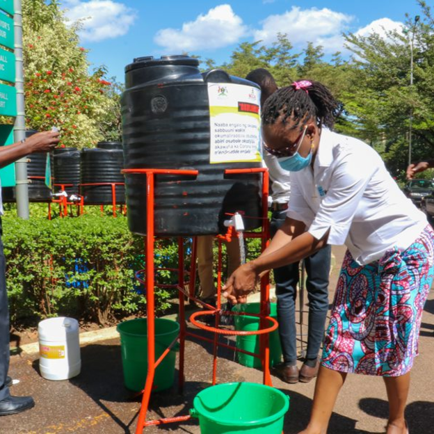 WaterAid Uganda Country Director Jane Mselle Sembuche and Samuel Sserunkuma, Deputy Executive Director of the Kampala Capital City Authority, demonstrate how a handwashing tank works. WaterAid provided the city with more than 60 handwashing station in ...