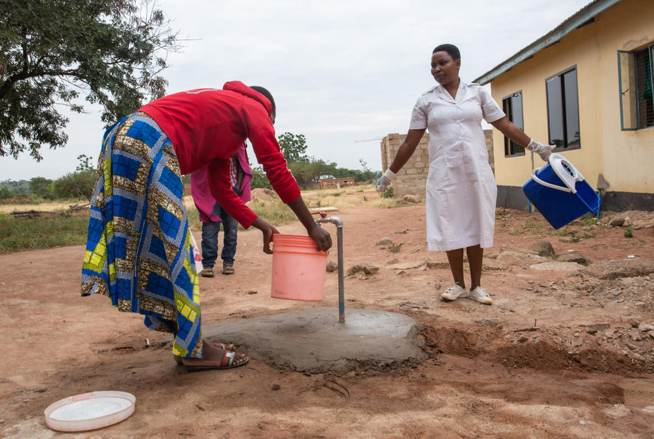 Nyaganga Juma Samuel, 37, nurse and midwife, collecting water from the tap to clean her work area, Nyamalimbe Dispensary, Geita District, Tanzania, June, 2019.