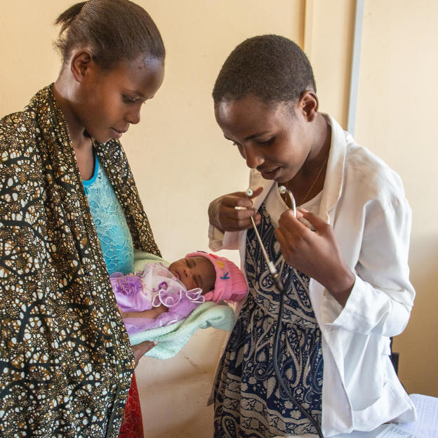 Avelina Alfred, 23, holding her baby as Dr. Queen Kulwa Machella, 24, Clinical Officer, examines her, Nkome Dispensary, Geita District, Tanzania, June, 2019.