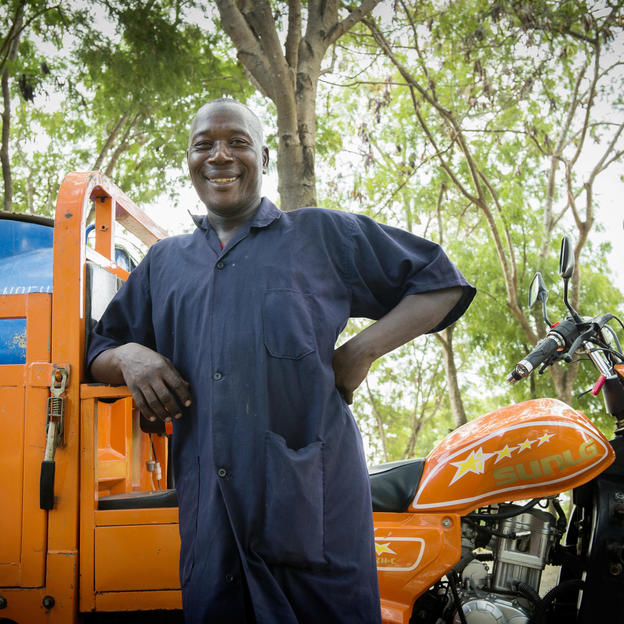 Julius Chisengo, Group Operator UMAWA, 48-years-old, stands next to one of the 'bajaj' vehicles that transports the gulper pump equipment, outside the plant at Kigamboni Ward, Temeke Municipality, Dar es Salaam City, Tanzania - February 2015.