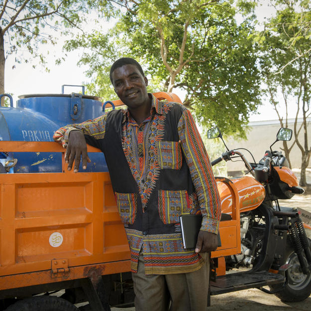 Mattius Millinga, 51-years-old, stands next to one of the 'pajaj' vehicles that transports the gulper pump equipment, outside his house in Kigamboni Ward, Temeke Municipality, Dar es Salaam City, Tanzania - February 2015.