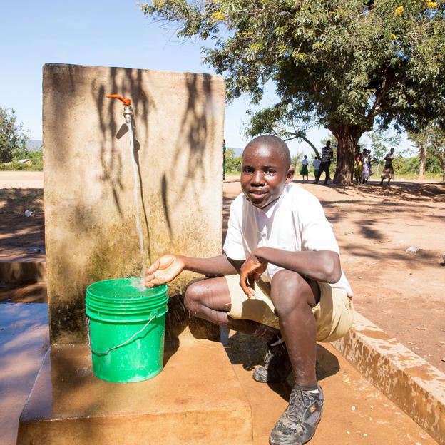 Richard, 17, Standard 7 pupil and member of the School Health Club at Kakora Primary School collecting water from newly built school water tap,  Kakora Primary School, Nyanghwale District, Tanzania, June 2018.