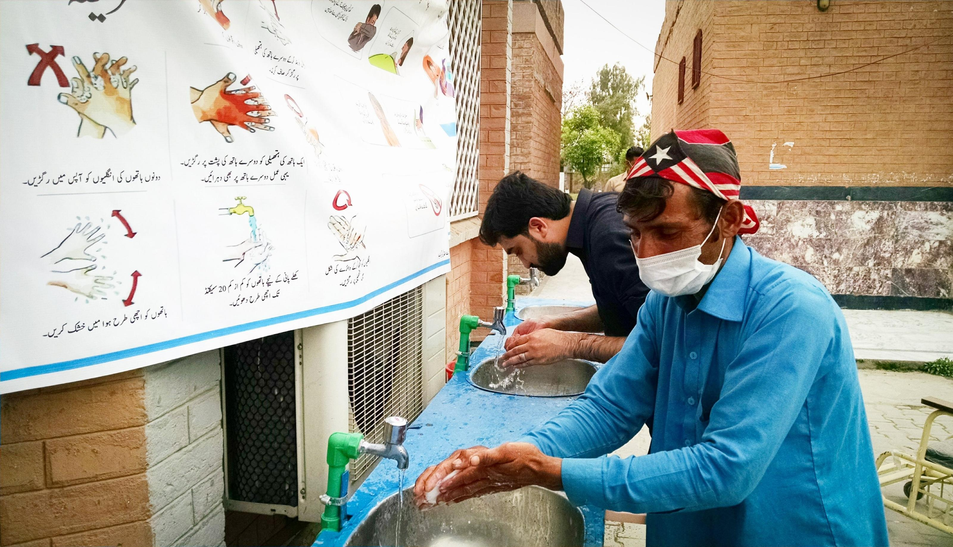 2 men using a handwashing station at Mardan Medical Complex outside its quarantine and emergency centres in Pakistan