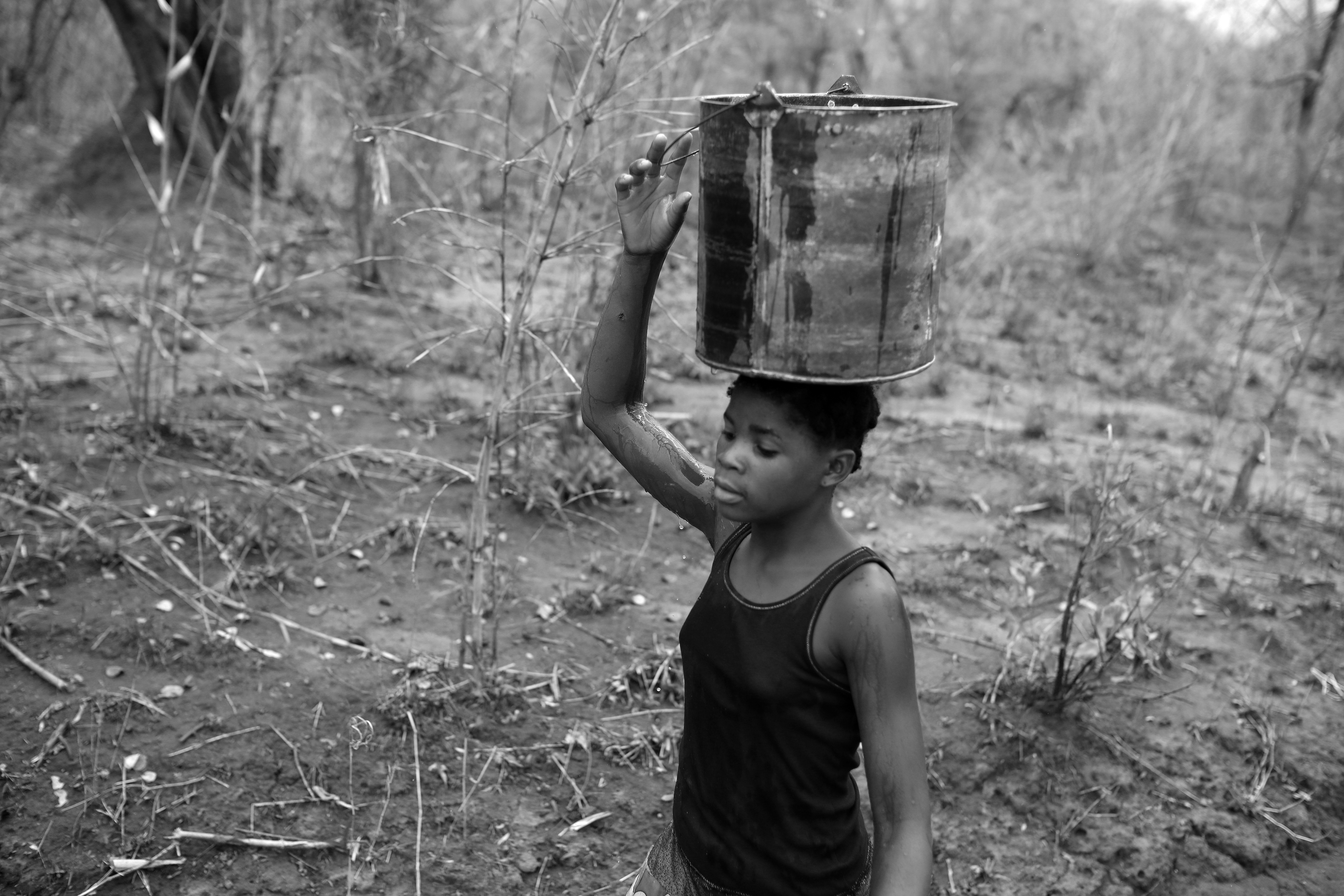 Josefina carries water home from a stagnant stream, Niassa, Mozambique.