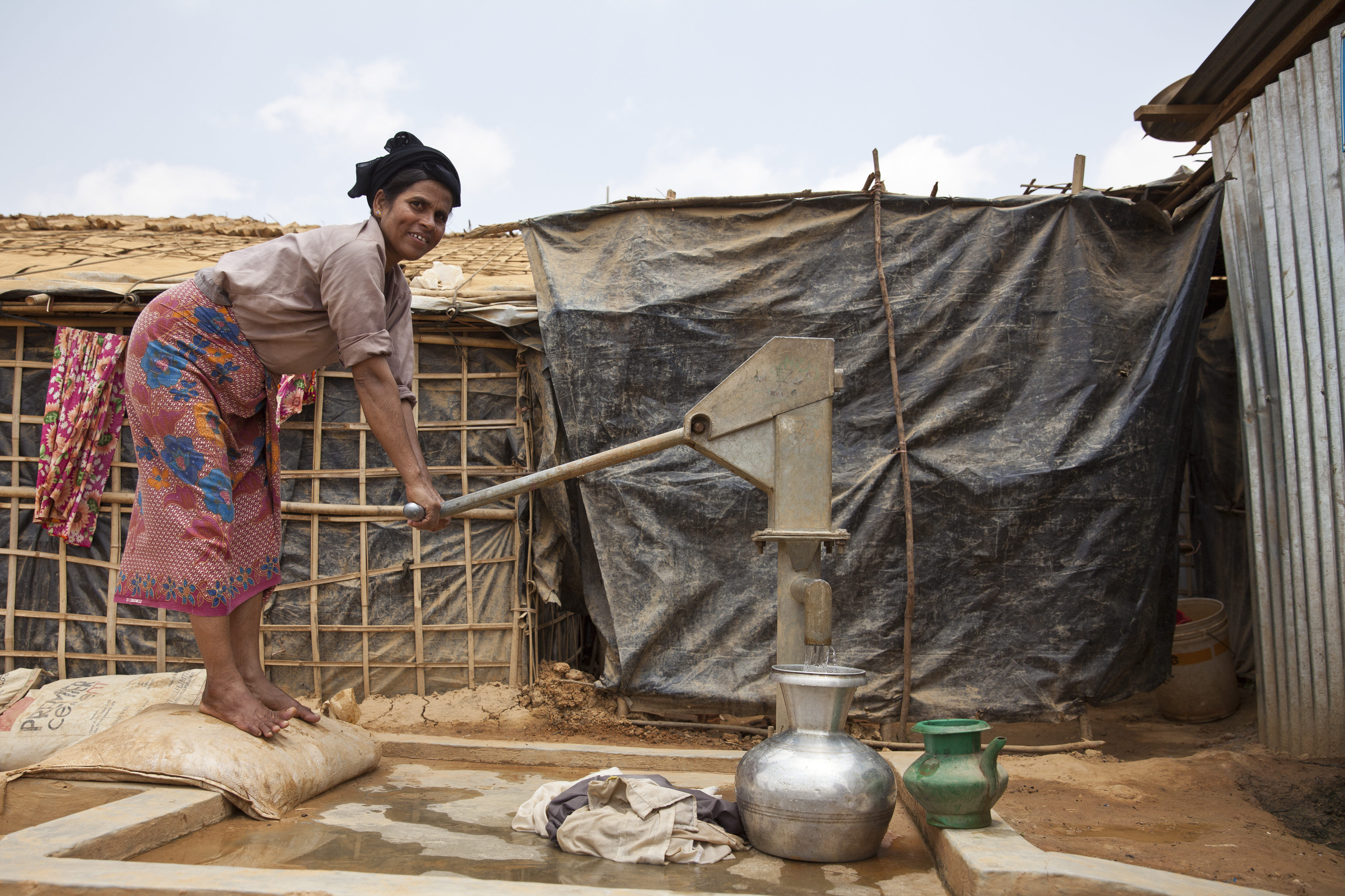 A Rohingya woman uses a WaterAid-built pump installed on top of a tube well