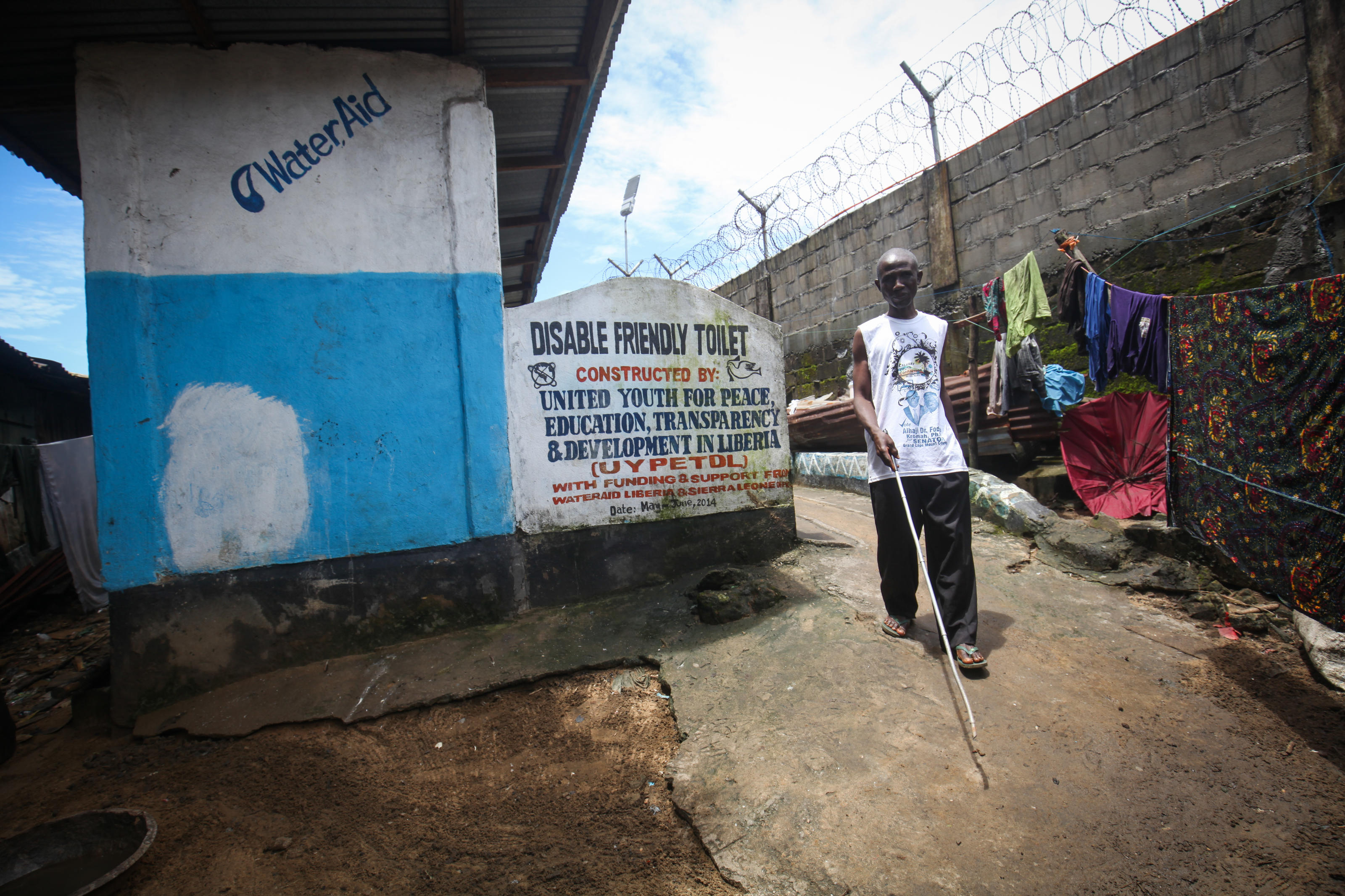 Johnson walks out of the disabled-friendly toilet at 17th Street, Sinkor, Monrovia, Liberia