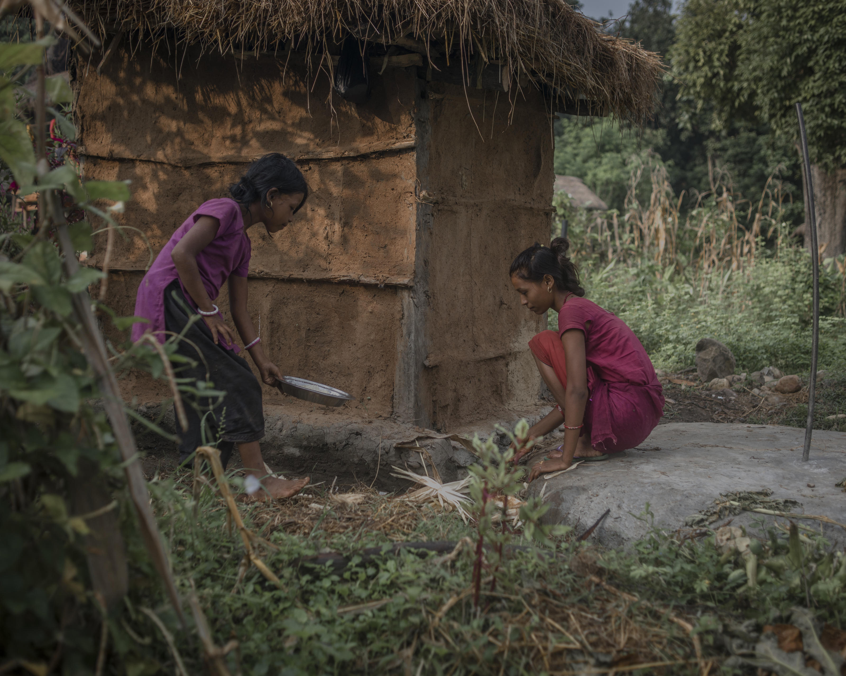 Radha, 16, behind the toilet where she is served food (boiled rice only) during chaupadi, Surkhet district, Nepal.