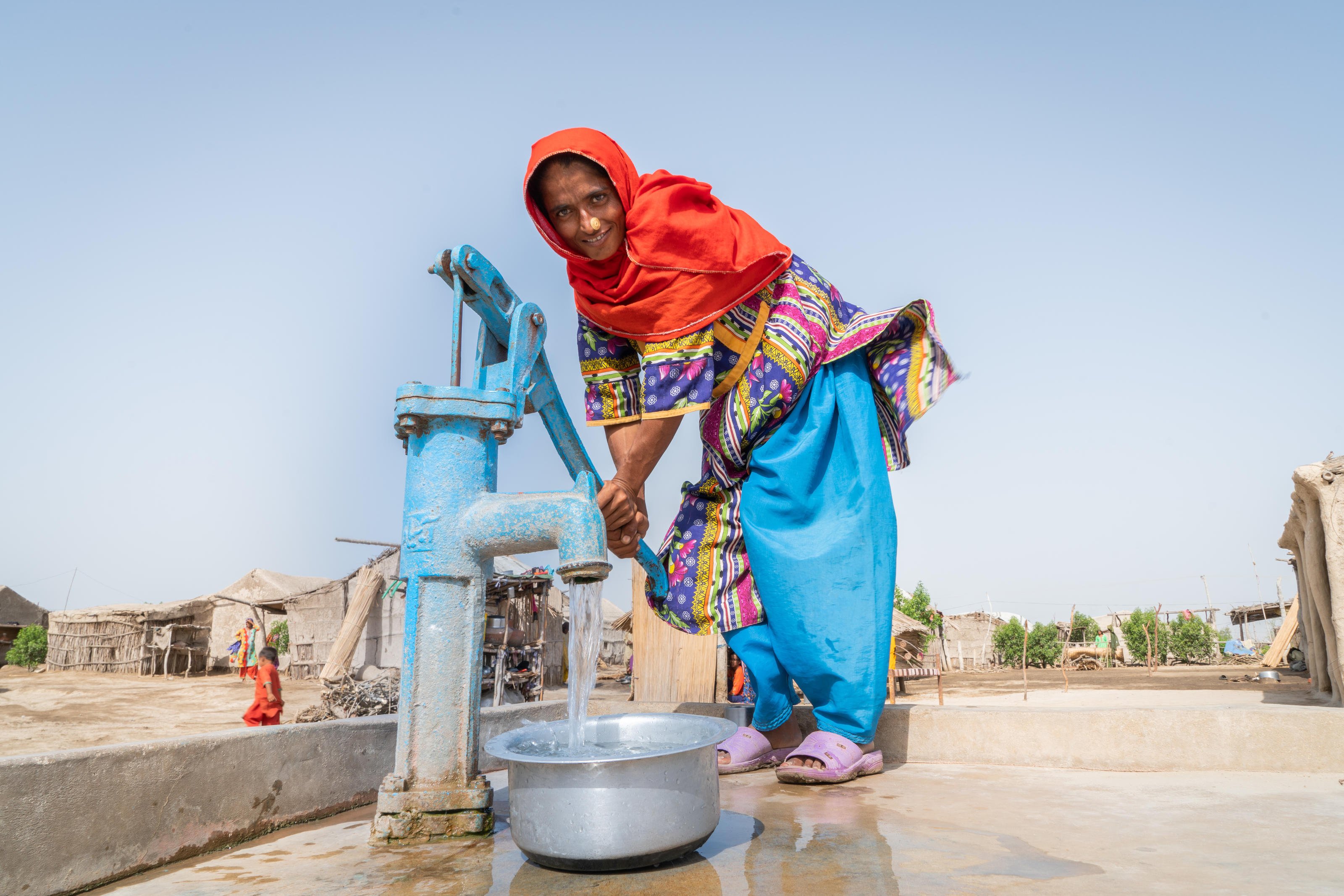 Zainab, 35, fetching water from a WaterAid installed pump in the village of Tamachi Mallah, Union Council Doomani,  District Thatta, Province Sindh, Pakistan, May 2018.