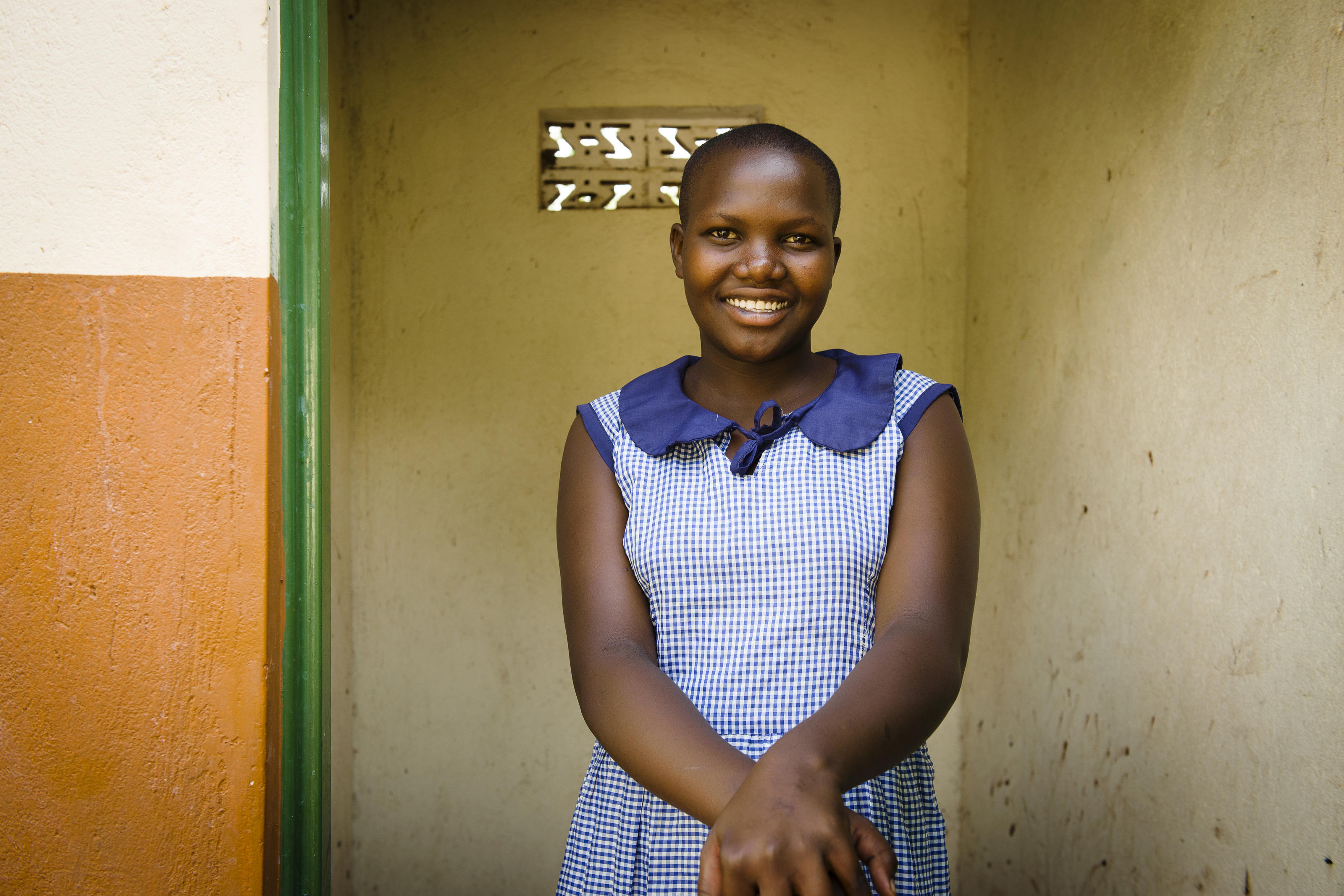 Sharon, WASH Club member, stands outside the newly built WaterAid latrine block at St Mary's School in Uganda.