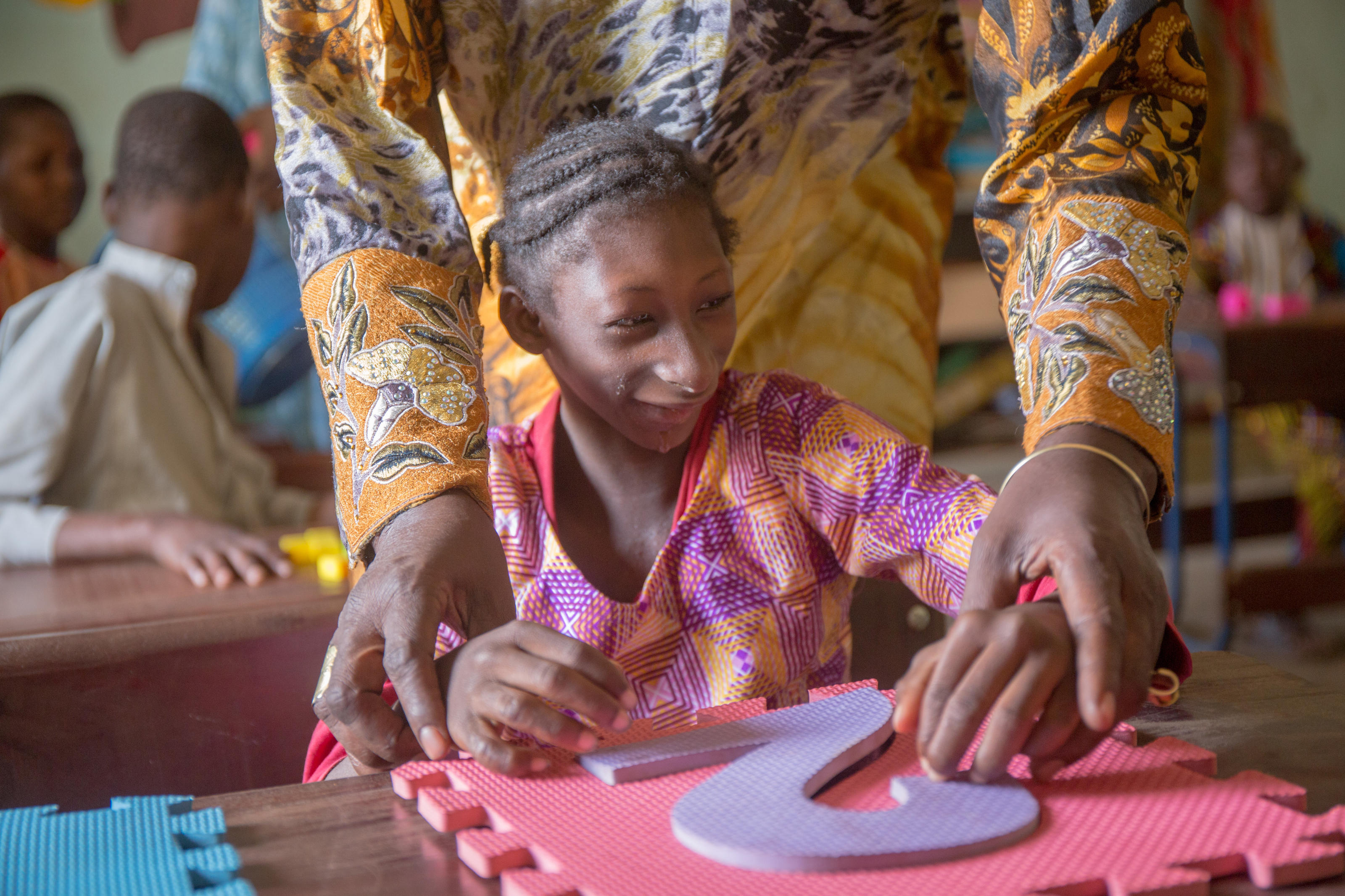 A girl with learning difficulties doing some exercises with a teacher in AMALDEME's special school in Mali