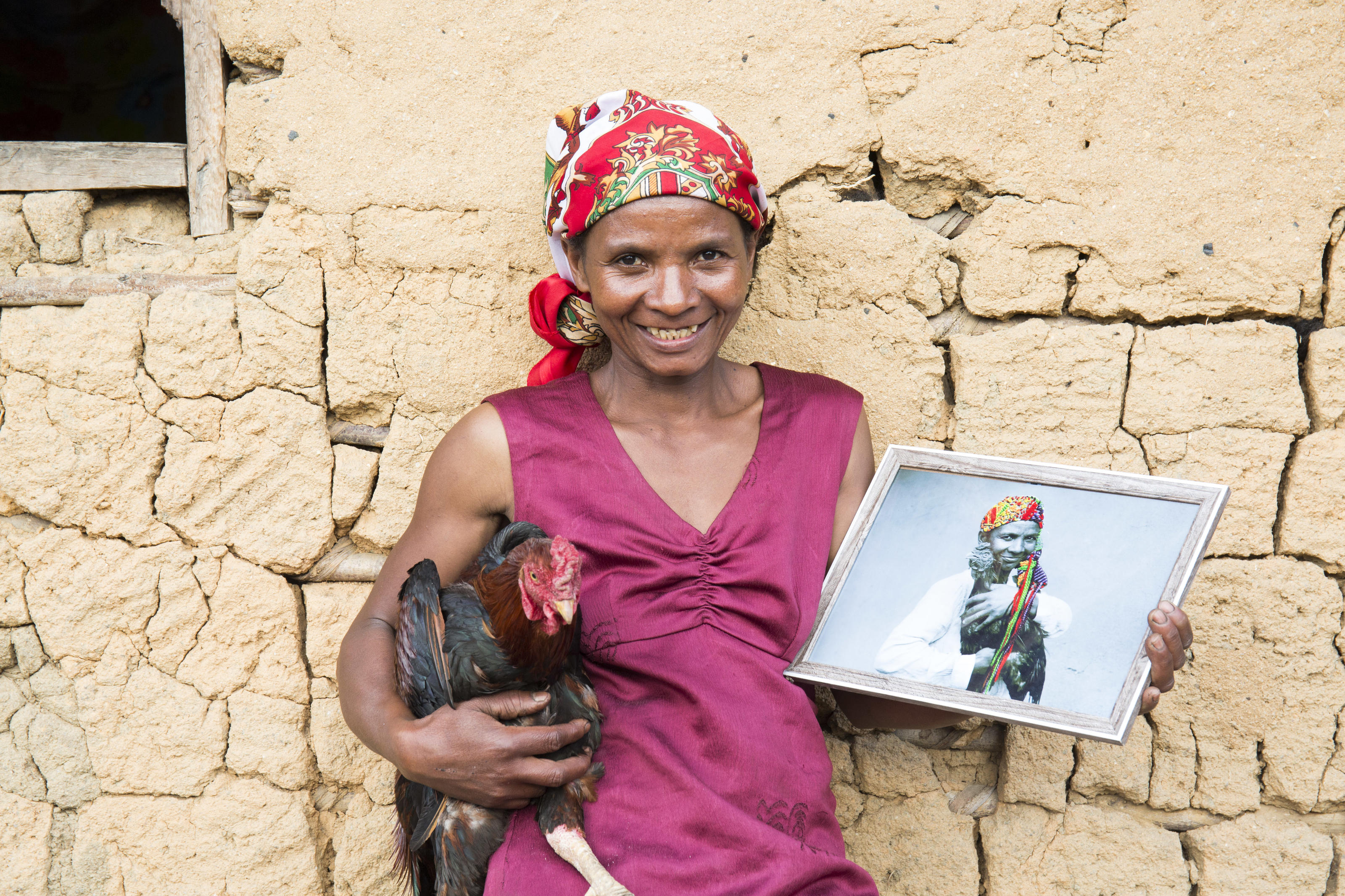 """This is amazing, I love it."" Portrait of Veronique Eulalie Rasoarimanana outside her home holding the photograph of her which includes the embroidery by Victoria Villasana.   Tsarafangitra village, Belavabary commune, Moramanga district, Alaotra Mangoro region, Madagascar. August 2018."