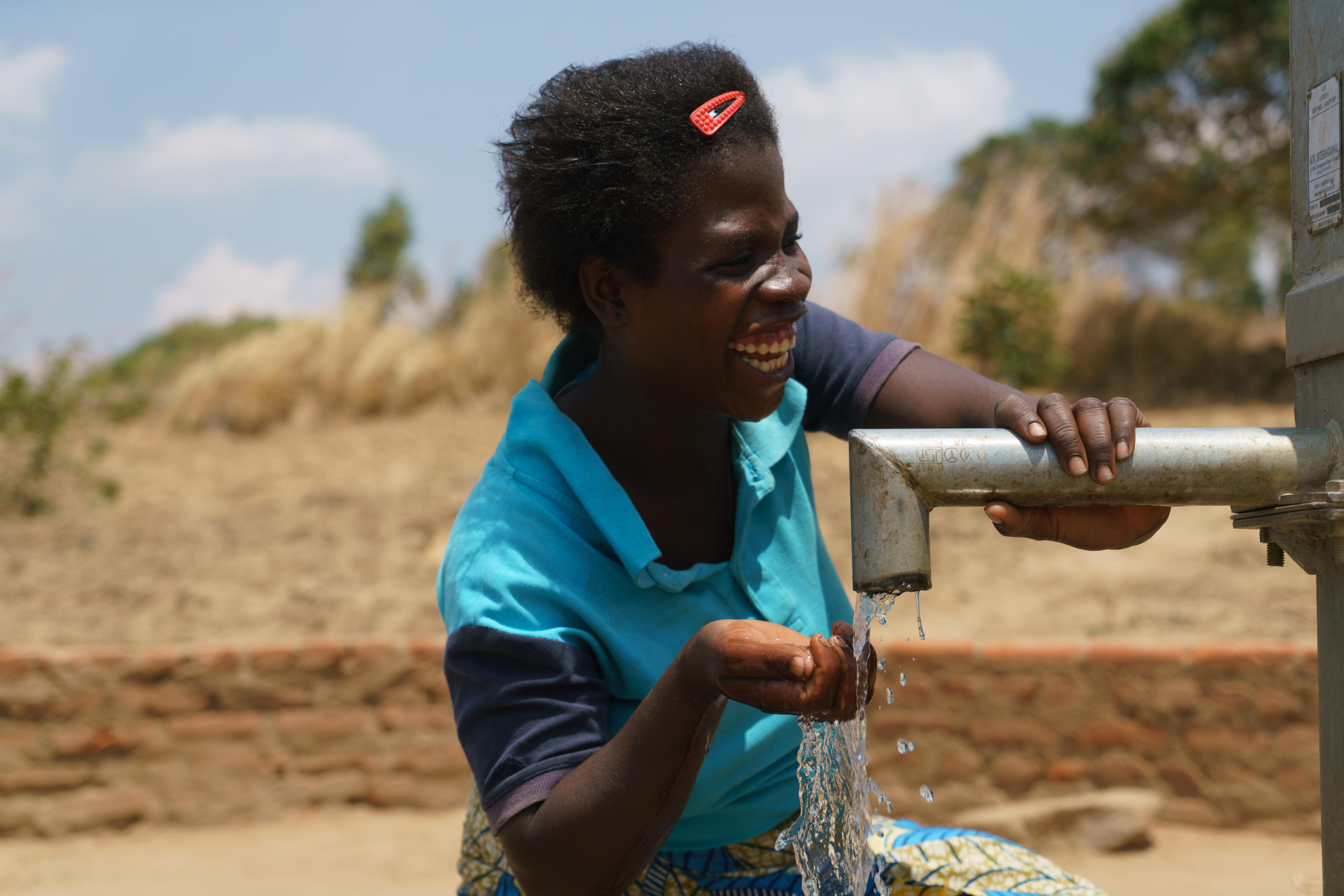 Esnart, 22, drinking water from the borehole in Vimphere Village, Malawi, September 2017