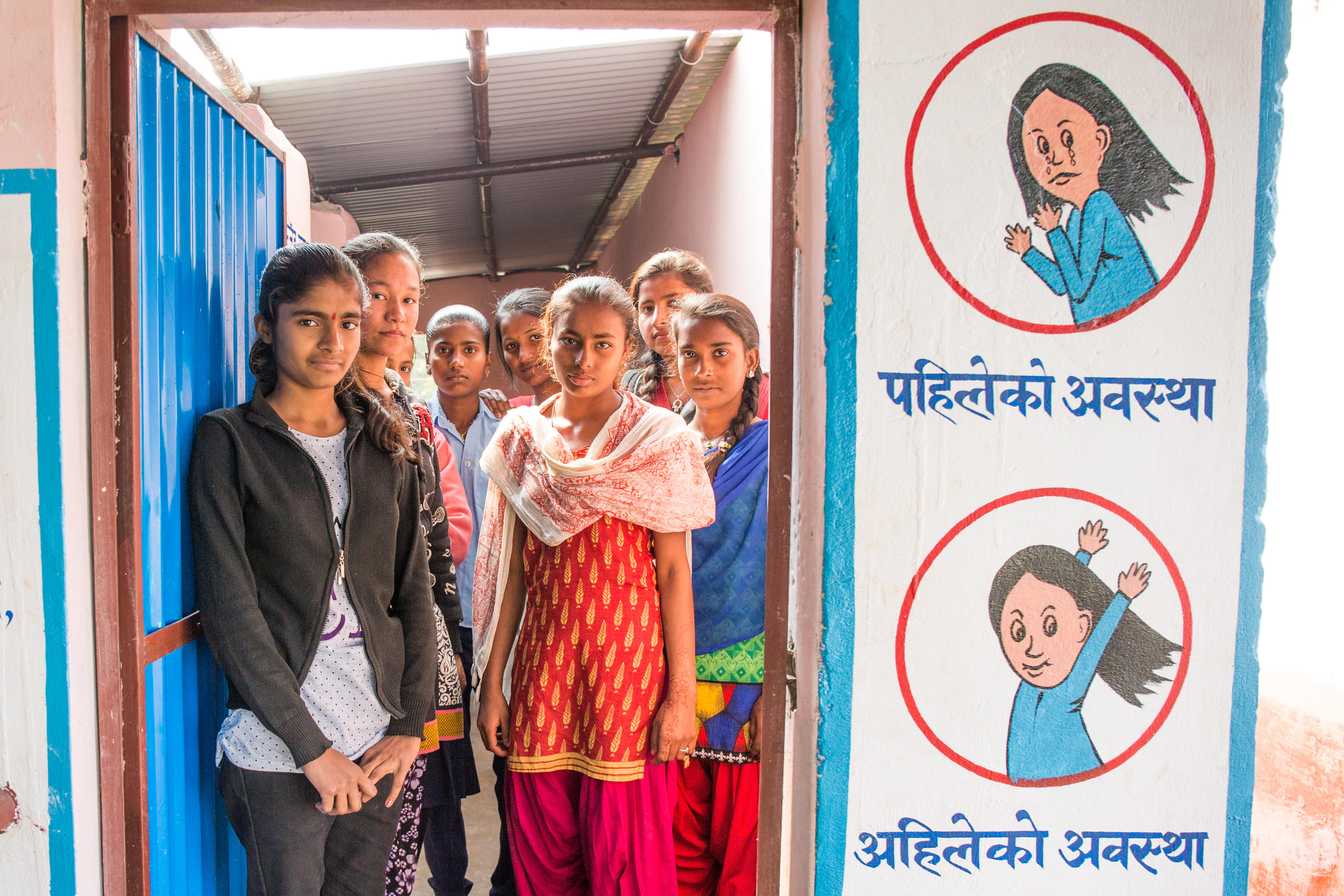 Bina,15, with her friends posing in front of their newly constructed girls friendly latrine at their school, Nepal.