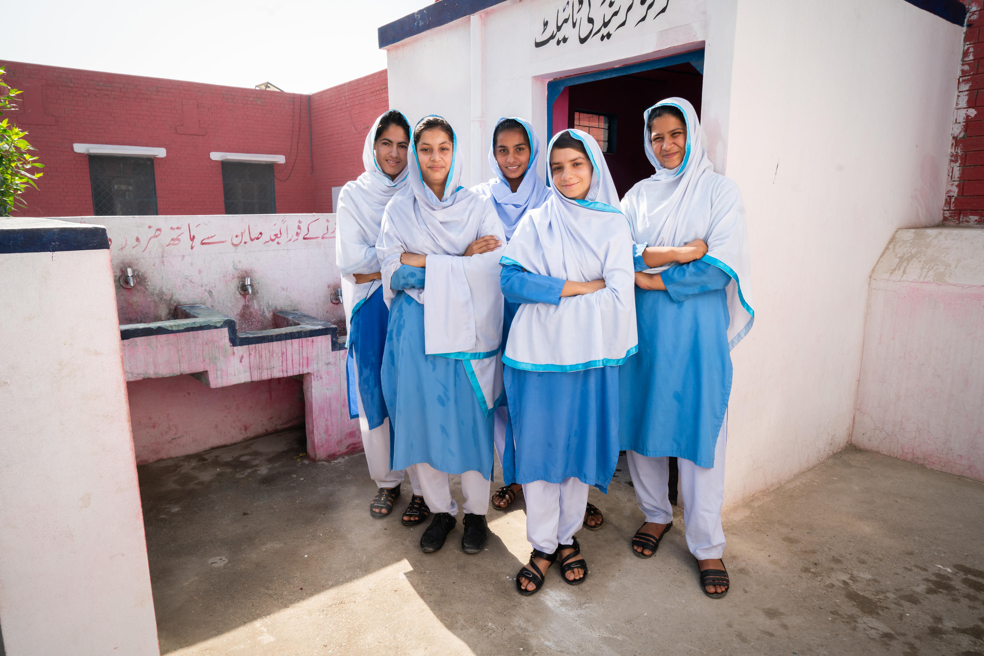 WASH group members, (left to right) Kiran, Mahwish, Saba, Ramsha and Iqra, in front of the WaterAid installed girls' friendly toilet in Government Girls High School Chak, Pakistan.