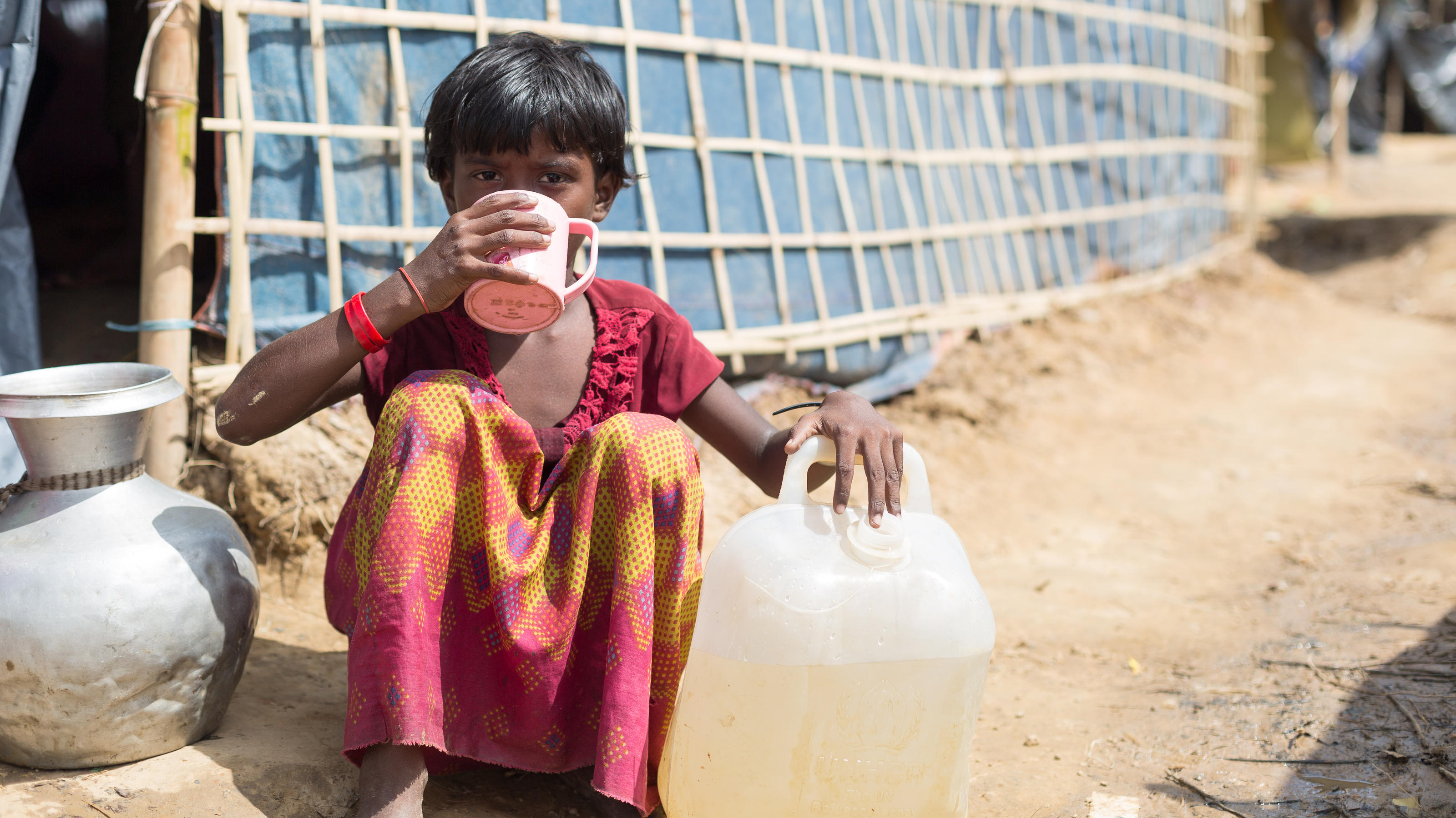 A young Rohingya girl takes a water break on her way uphill to her family's temporary shelter at the Kutupalong Camp in Cox's Bazar