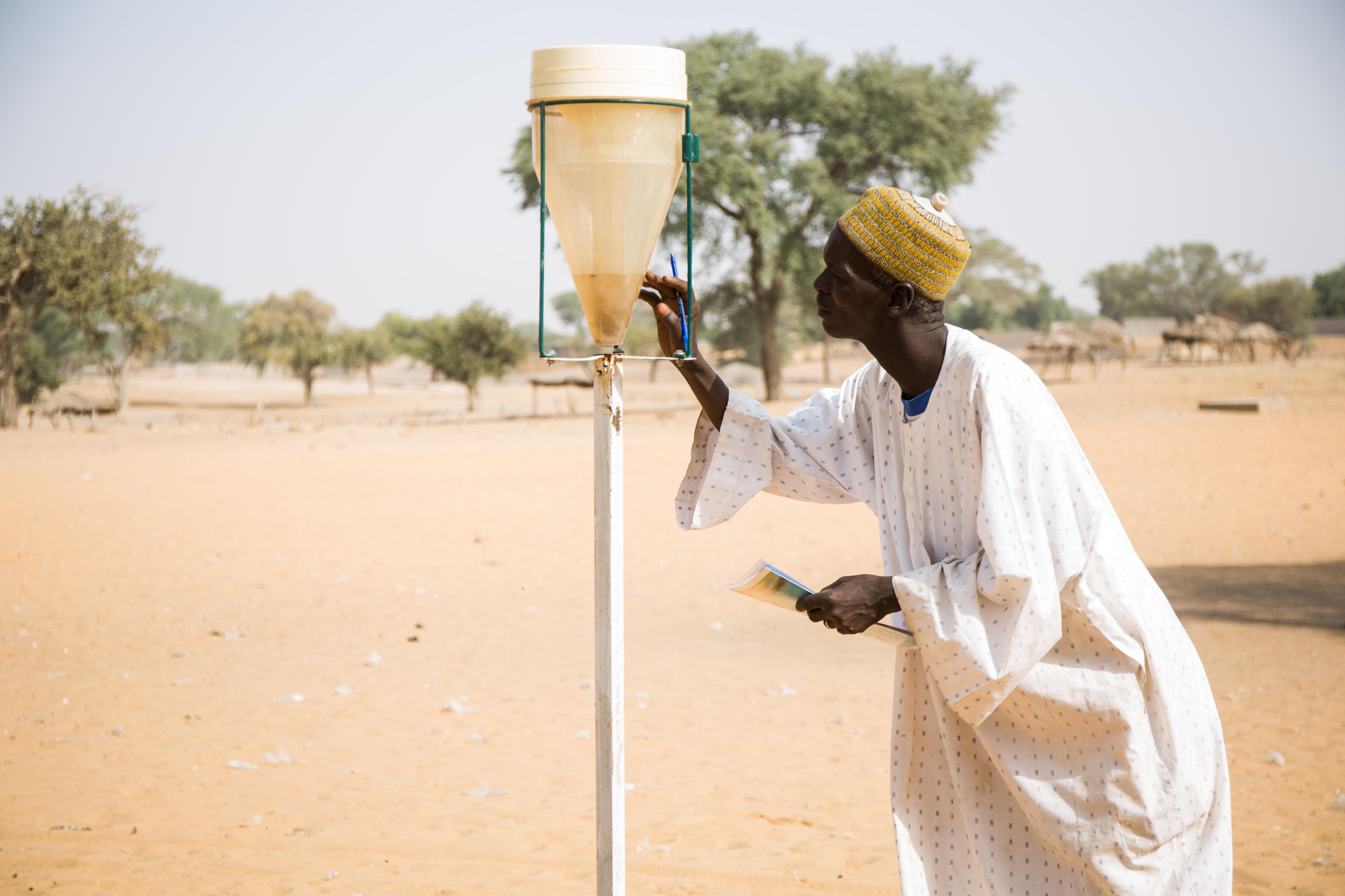 Ali Sabo, 51, a water monitor, demonstrating how he uses a rain gauge to monitor rainfall, Dungass, in the department of Dungass, Zinder, Niger, February 2019.