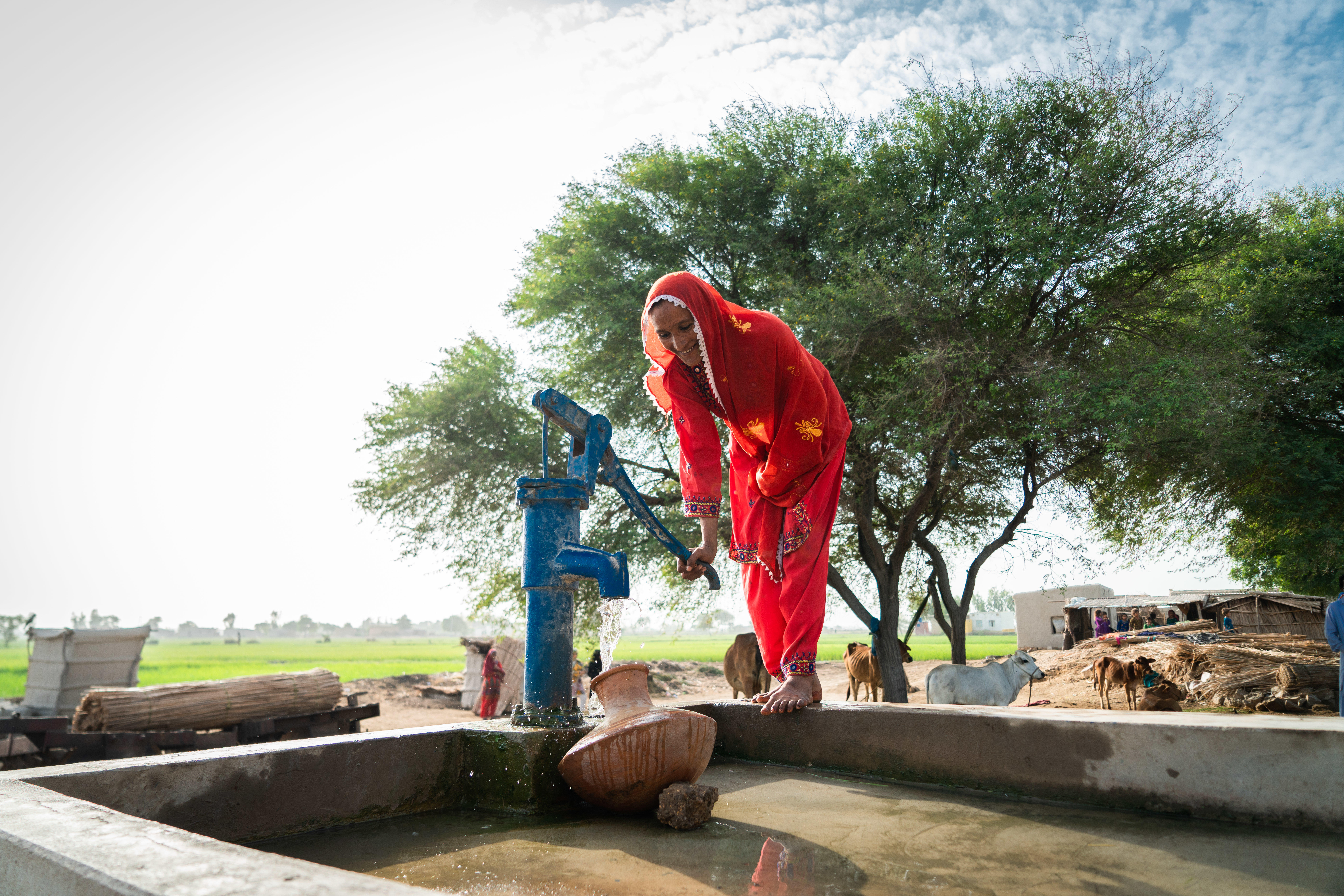 Amina fetching water from a WaterAid installed hand pump close to her home in Pakistan.