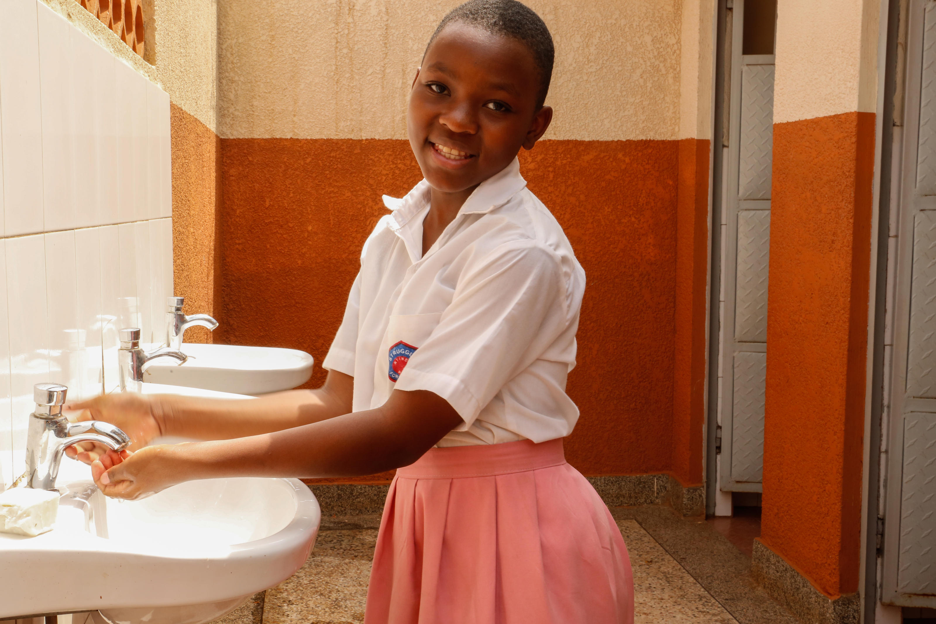 Catherine, 13, student, washing her hands at a newly installed sink in the girls' toilet block, Uganda.