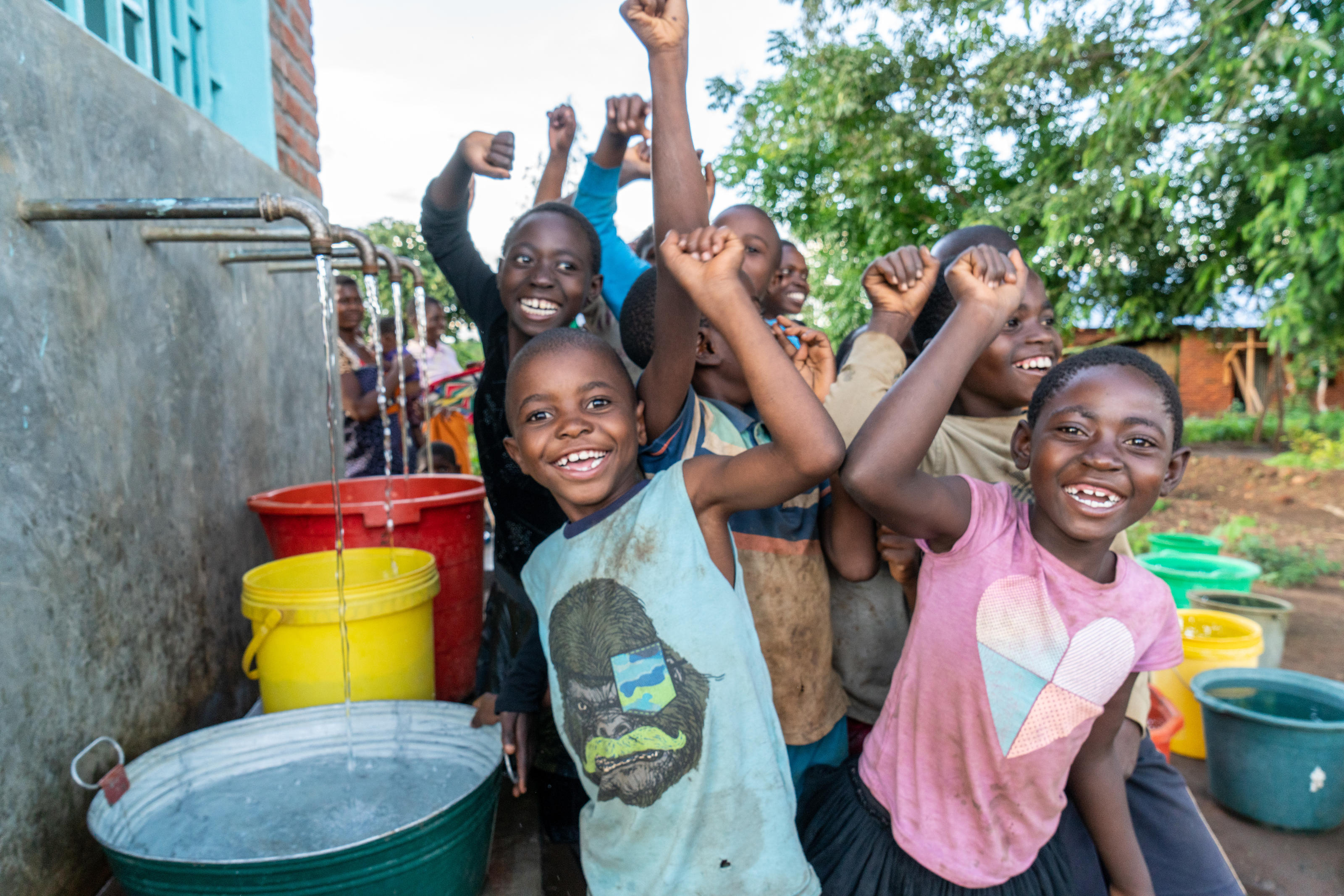 Children from Chiswe village collecting clean water from the new water kiosk.