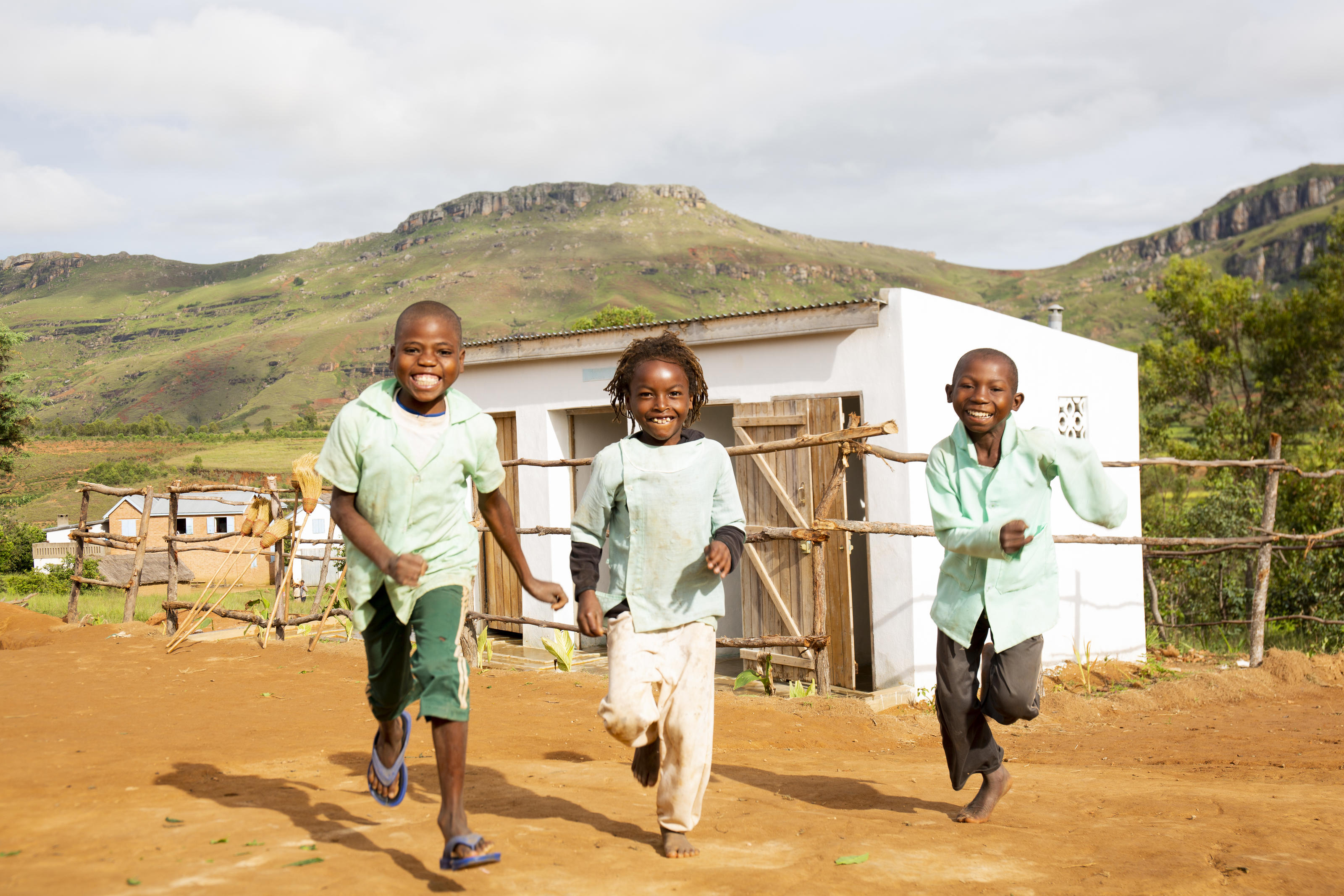 Bera, Toky and Samy running in front of their new sanitation block at their primary school in Madagascar
