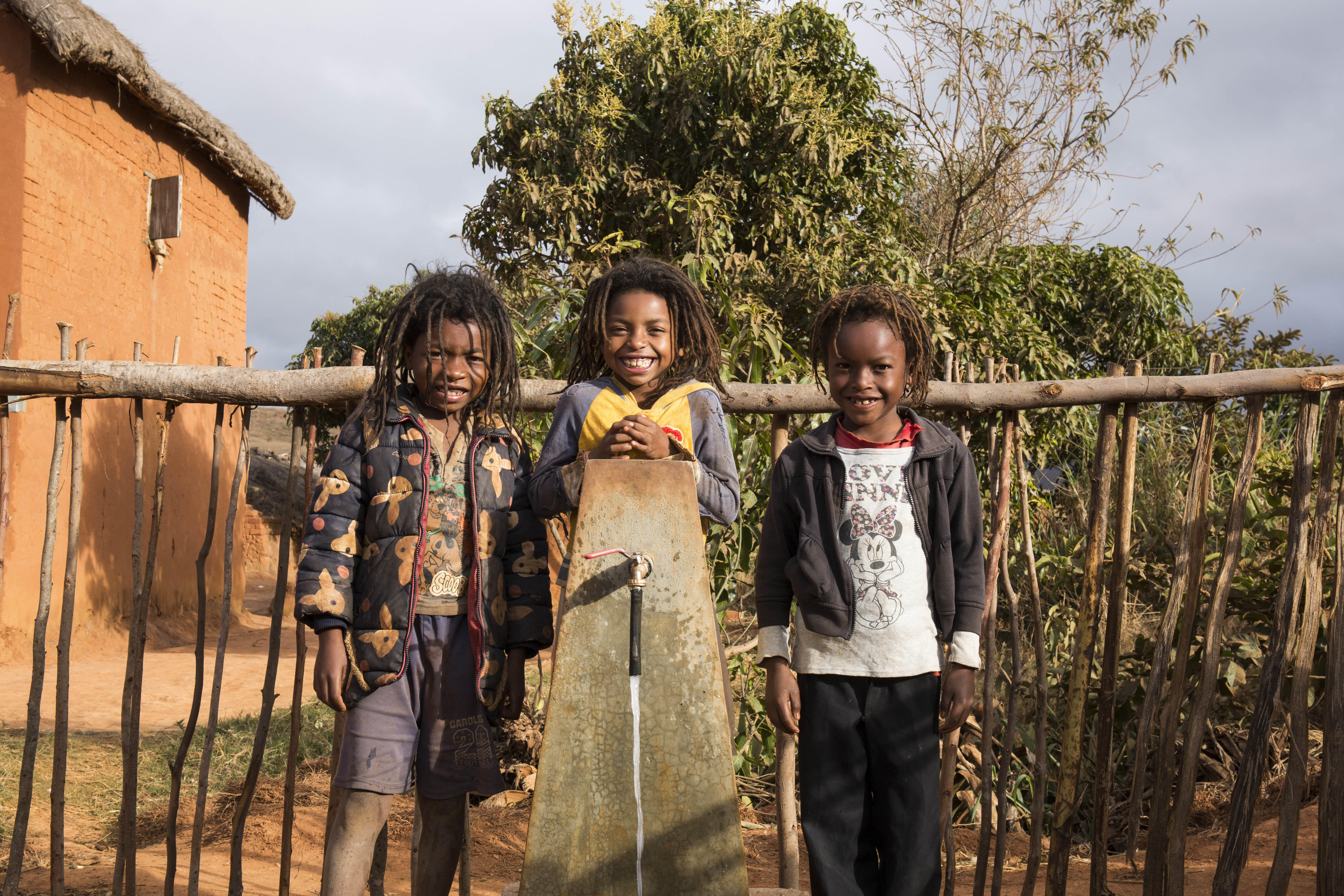 Faly, 9, with his sister and brother who are twins, Kanto and Toky, 6 at their new water point near their home.