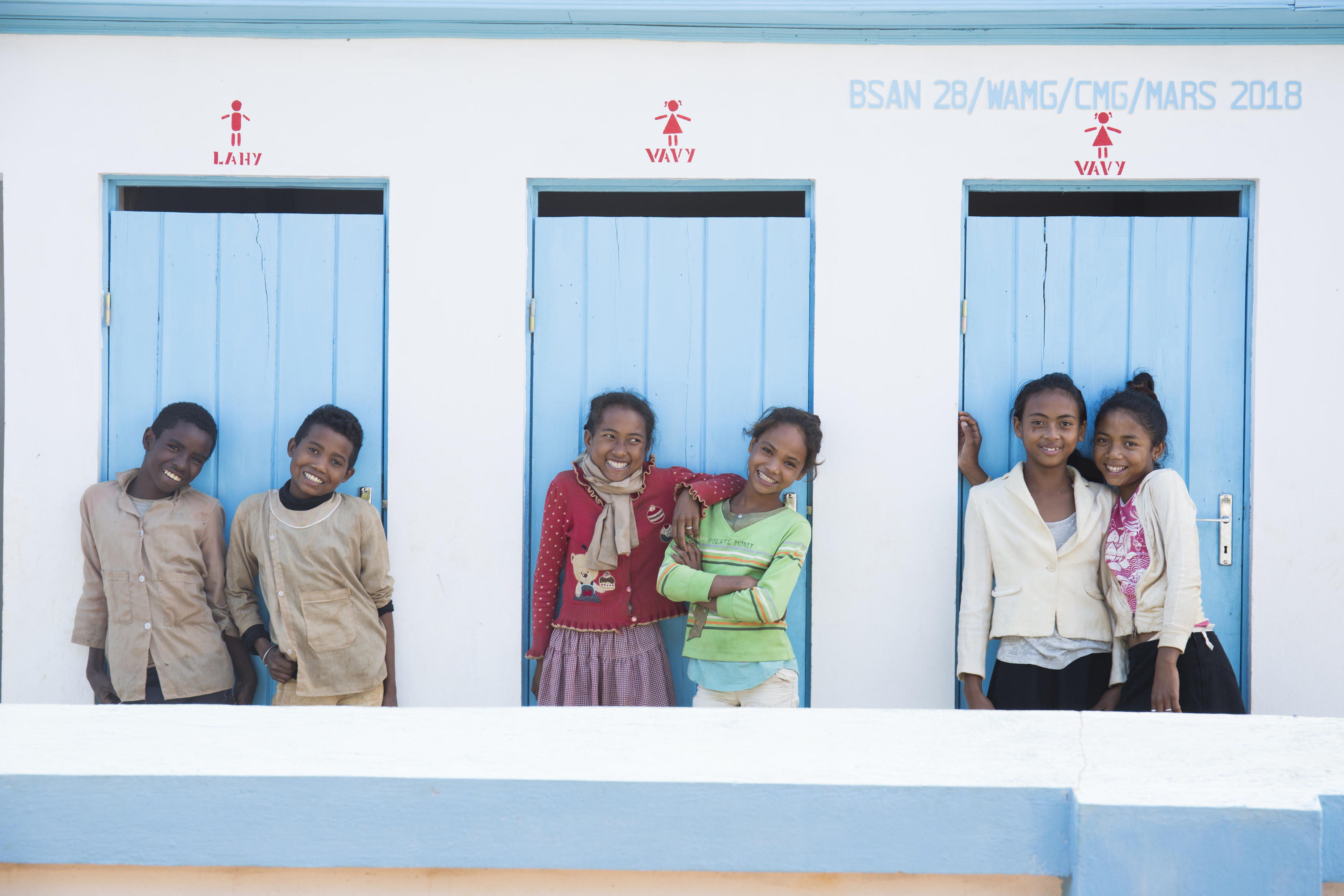 From left to right, Fetra, 12, Tongasoa, 13, Hasina, 12, (red top) Hanitrasoa, 11, (green top), Andrea, 12, and Sarah, 13, posing in front of their separated toilet block. Primary school of Firaisantsoa Imanga village, Tsinjoarivo Imanga commune, Tsir ...