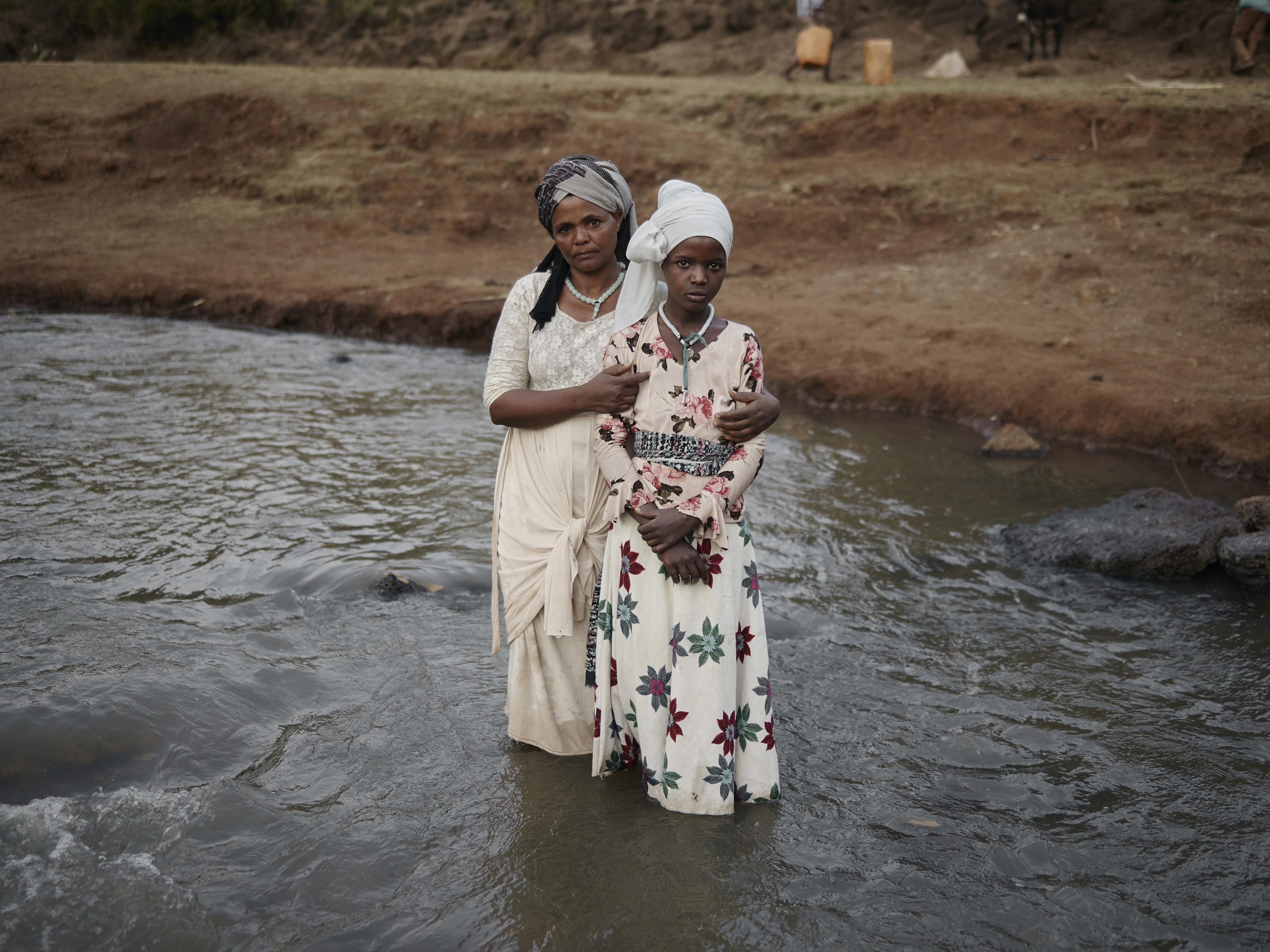 Hawa (44) with her daughter Ansha (12) standing in the River Lah in Frat, Ethiopia. February 2020. Ansha inspired the sand portrait on Whitby beach created by WaterAid in March 2020.