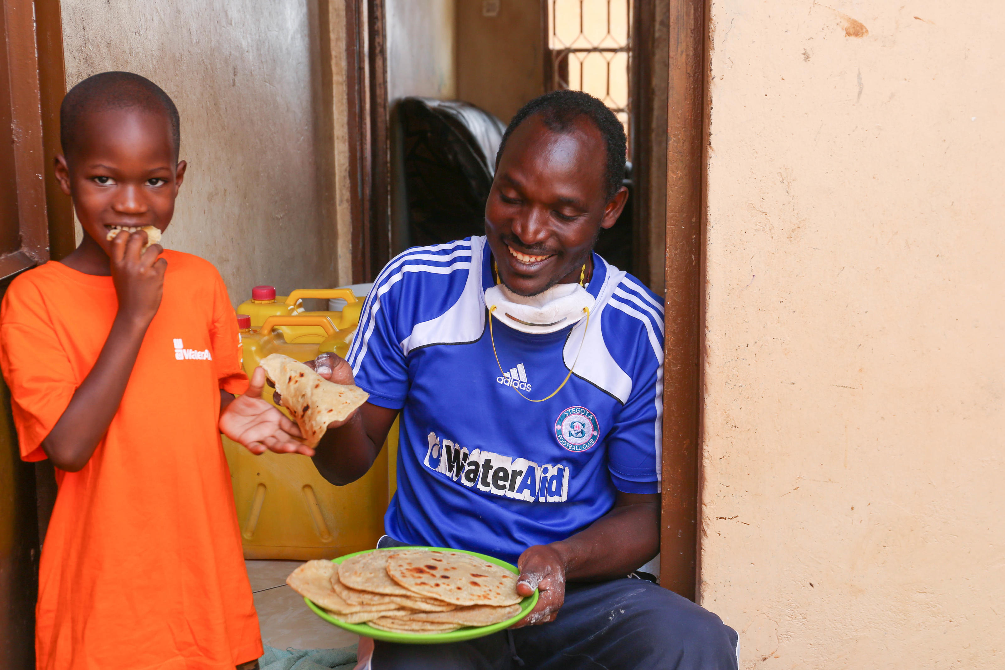 "James Kiyimba serving his son Claver, 6, the homemade chapati. ""The chapati is most delicious when warm, just after flipping it"". Covid-19 response. Lockdown Diaries - James Kiyimba. Uganda. May 2020"