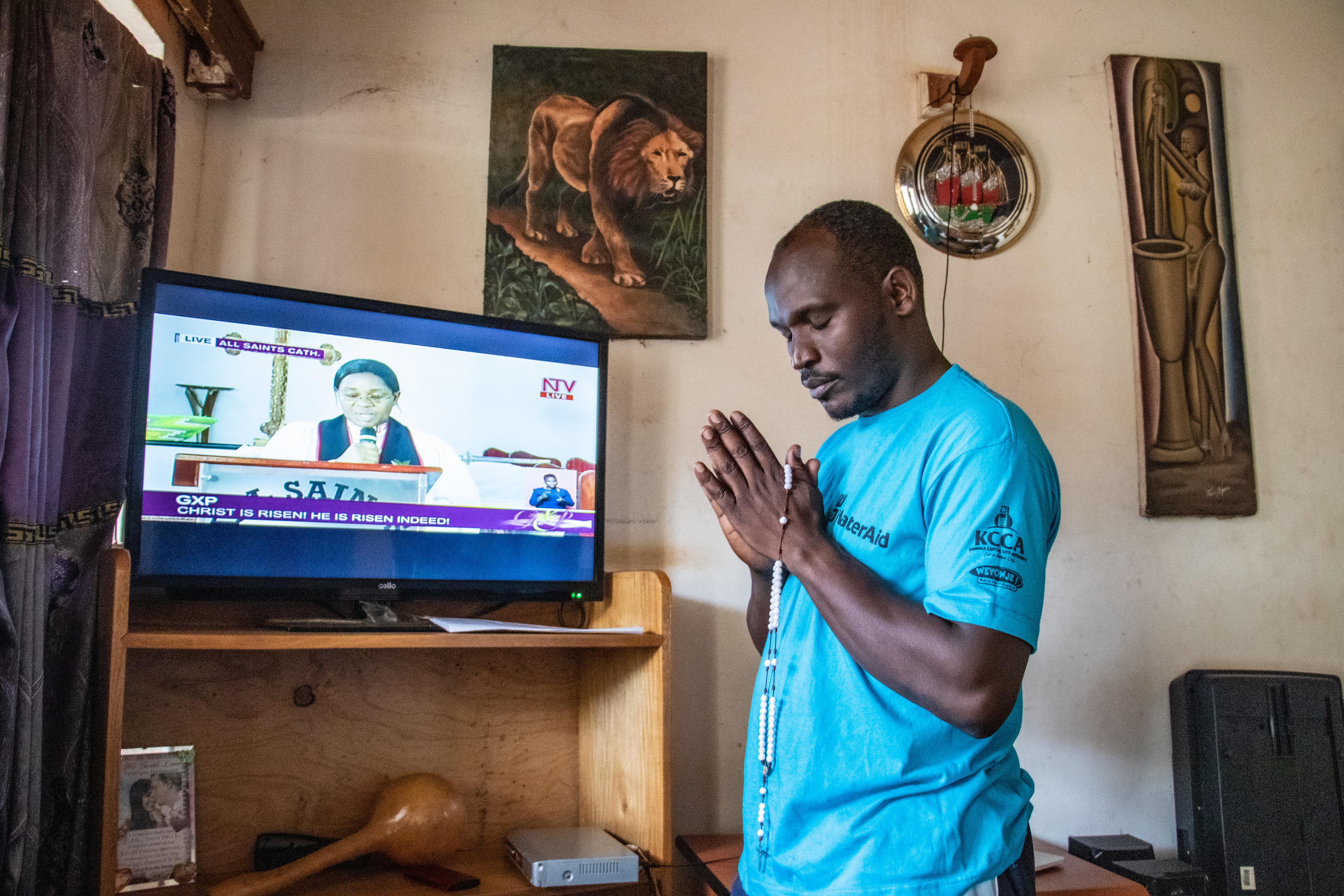 James Kiyimba, Voices from the Field Officer, WaterAid Uganda, attending a televised Easter Sunday church service from his home. Covid-19 response. Lockdown Diaries - James Kiyimba. Kampala, Uganda. April 2020